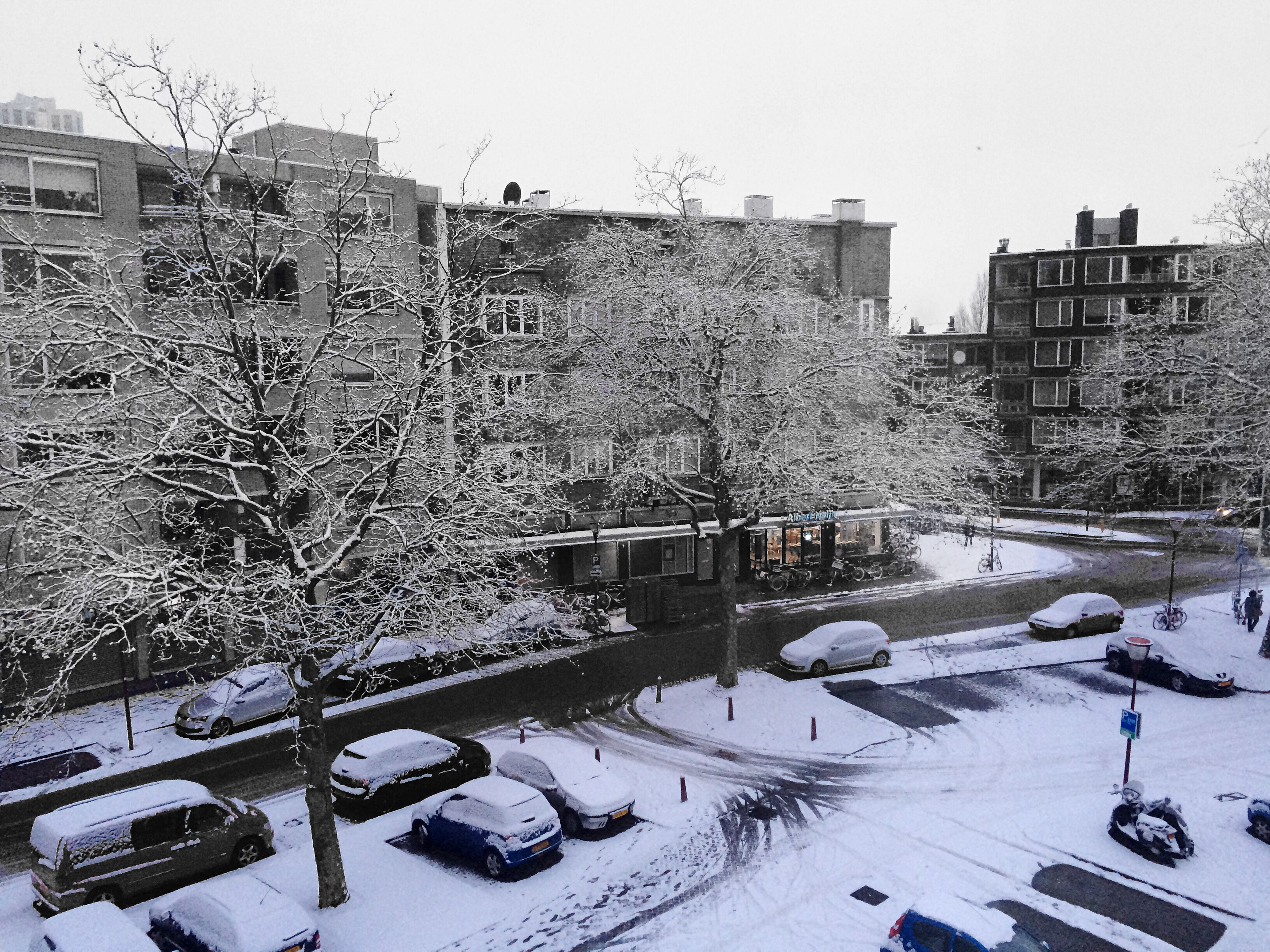 snow, winter, cold temperature, building exterior, architecture, transportation, built structure, land vehicle, season, car, weather, mode of transport, street, road, city, covering, high angle view, clear sky, day, bare tree
