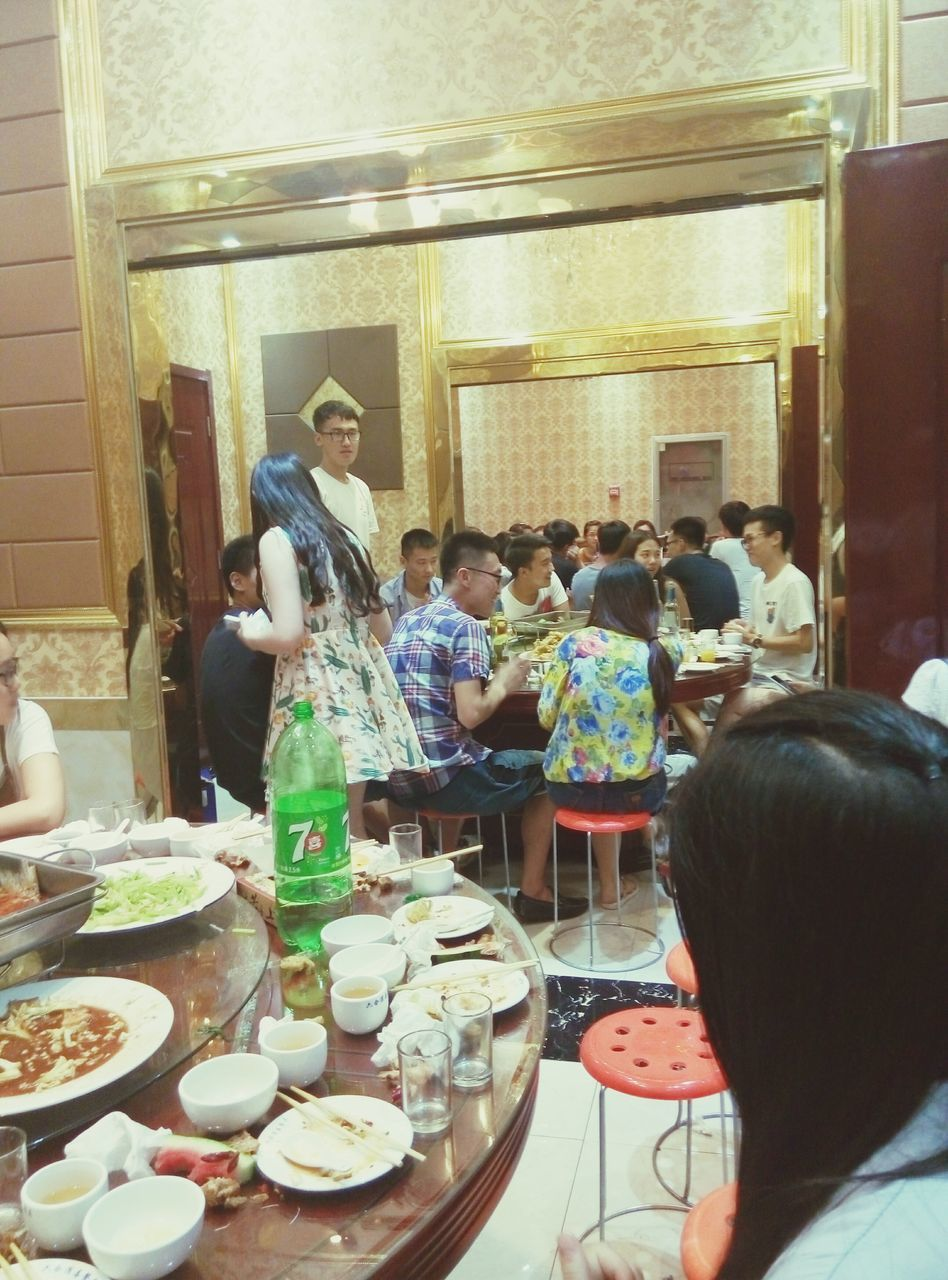 real people, food and drink, food, indoors, lifestyles, men, women, standing, plate, table, leisure activity, togetherness, sitting, large group of people, day, freshness, ready-to-eat, people