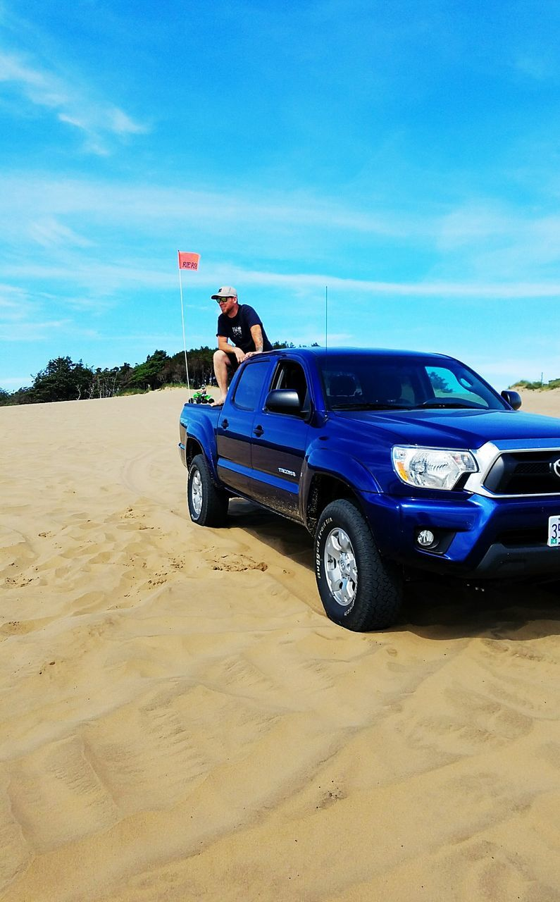 blue, sand, flag, car, beach, sky, transportation, day, cloud - sky, land vehicle, outdoors, sea, nature, horizon over water, one person