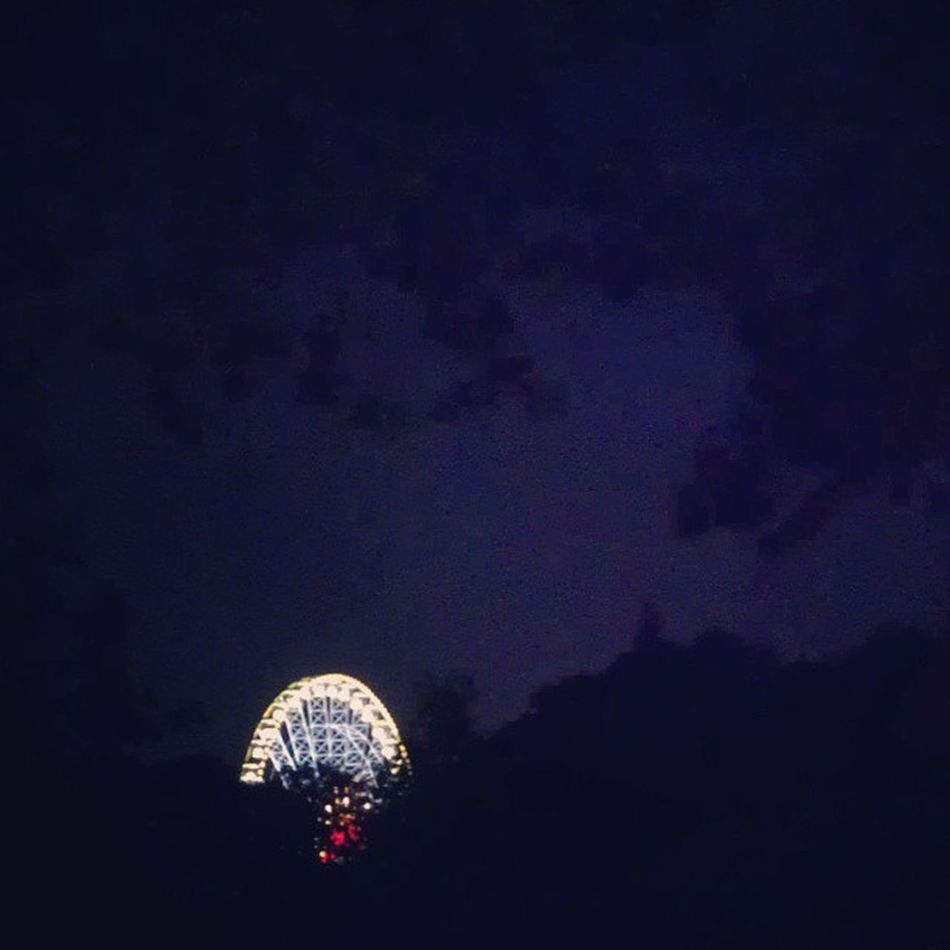 Fairground from a distance. Annual Fair Ferriswheel Schueberfouer luxembourg summer nighttime darkness treetops