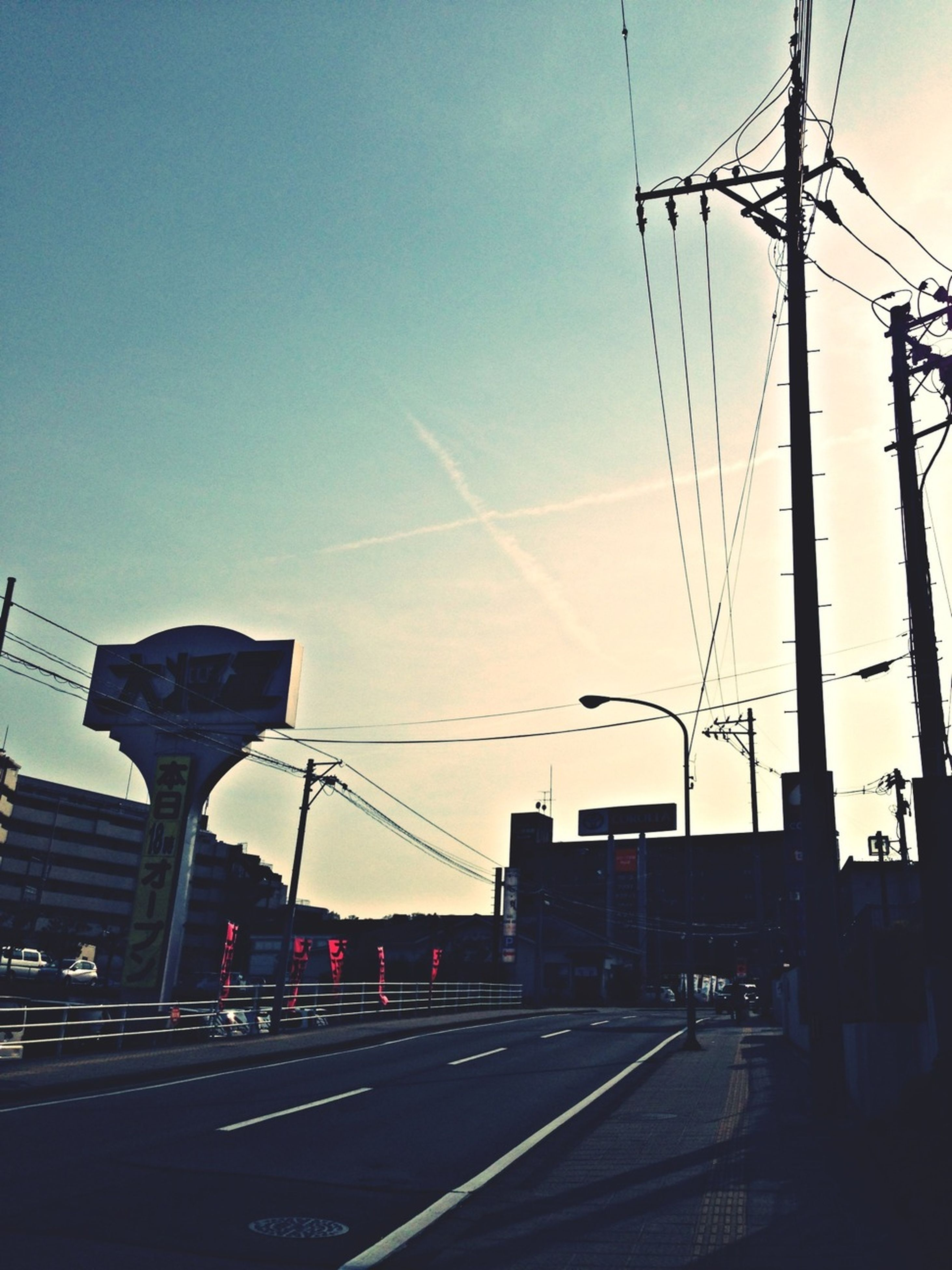 power line, building exterior, architecture, built structure, electricity pylon, cable, electricity, power supply, city, connection, sky, power cable, clear sky, transportation, silhouette, sunset, railroad track, fuel and power generation, low angle view, residential building