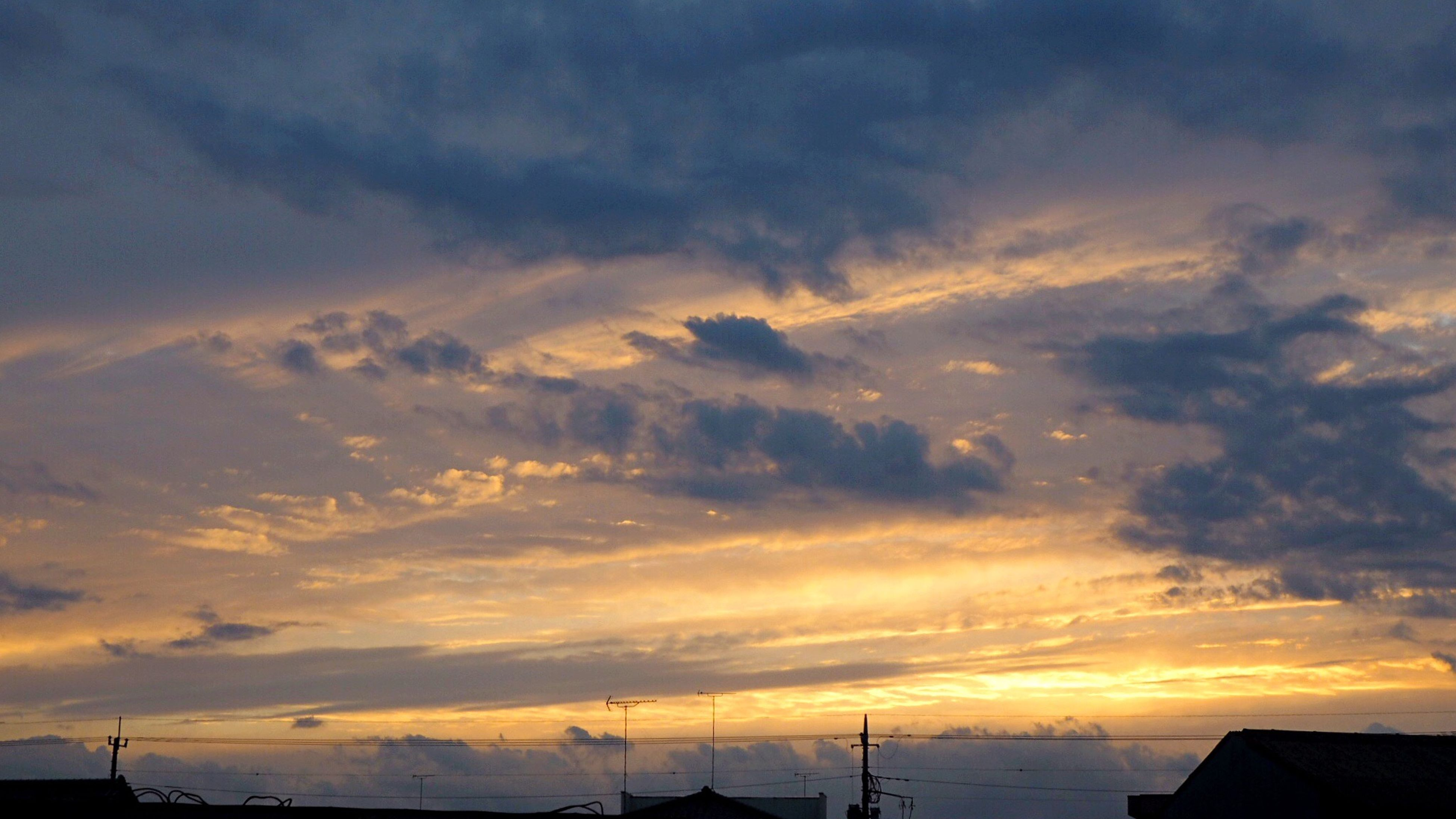 sunset, sky, silhouette, cloud - sky, orange color, beauty in nature, scenics, tranquility, tranquil scene, dramatic sky, cloudy, nature, weather, cloud, low angle view, idyllic, moody sky, built structure, outdoors, building exterior