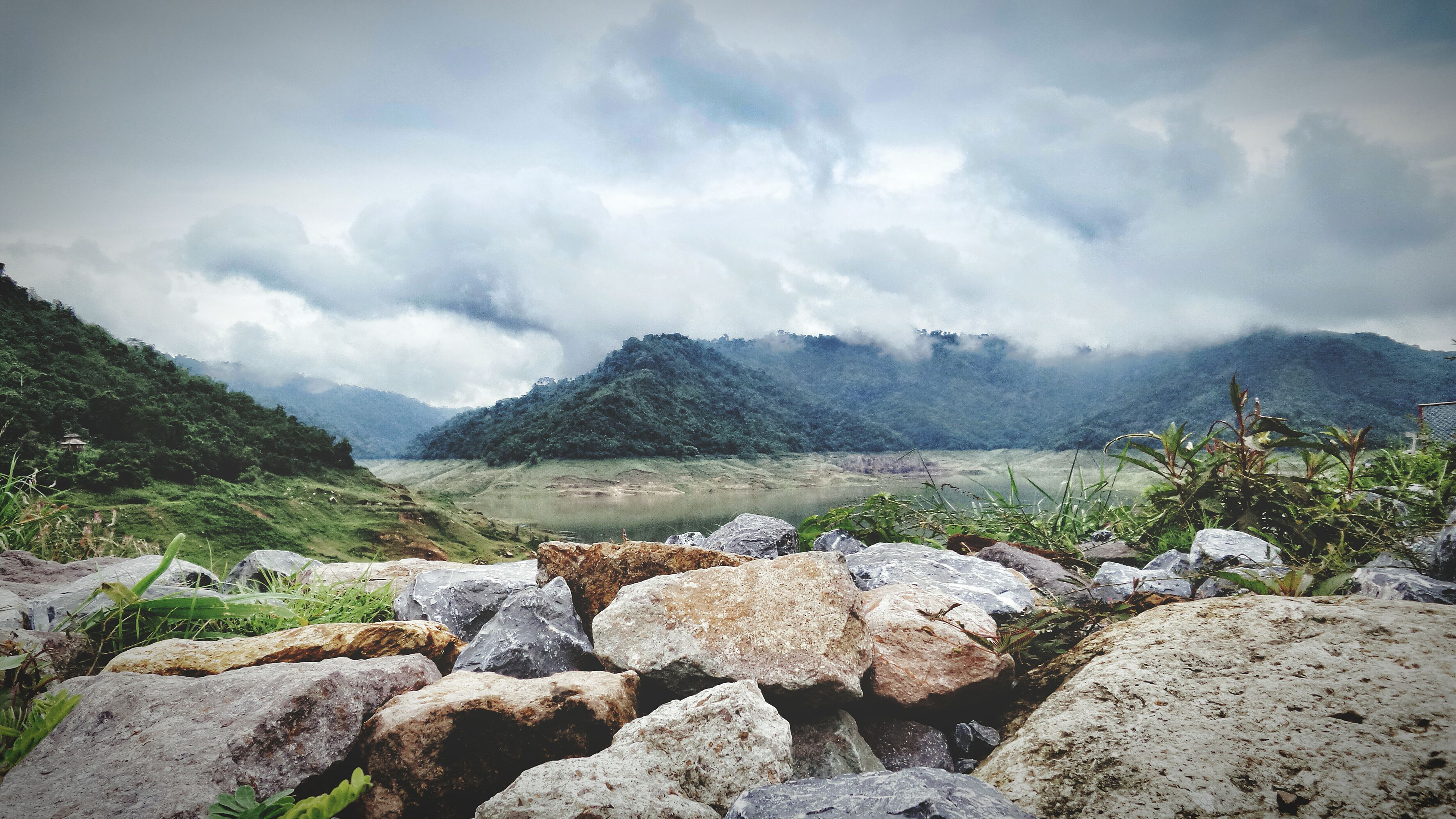 mountain, sky, mountain range, scenics, tranquil scene, tranquility, cloud - sky, beauty in nature, landscape, nature, rock - object, cloudy, non-urban scene, cloud, idyllic, rock formation, day, remote, hill, physical geography