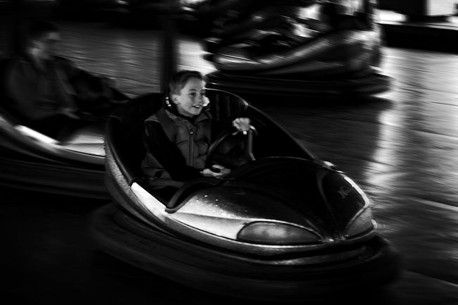 The first dodgem car ride Black And White Blackandwhite Blackandwhite Photography Boy Dodgem Cars Enjoyment Fairground Focus On Foreground Fun Leisure Activity Lifestyles Monochrome Portrait Selective Focus Sitting Smile