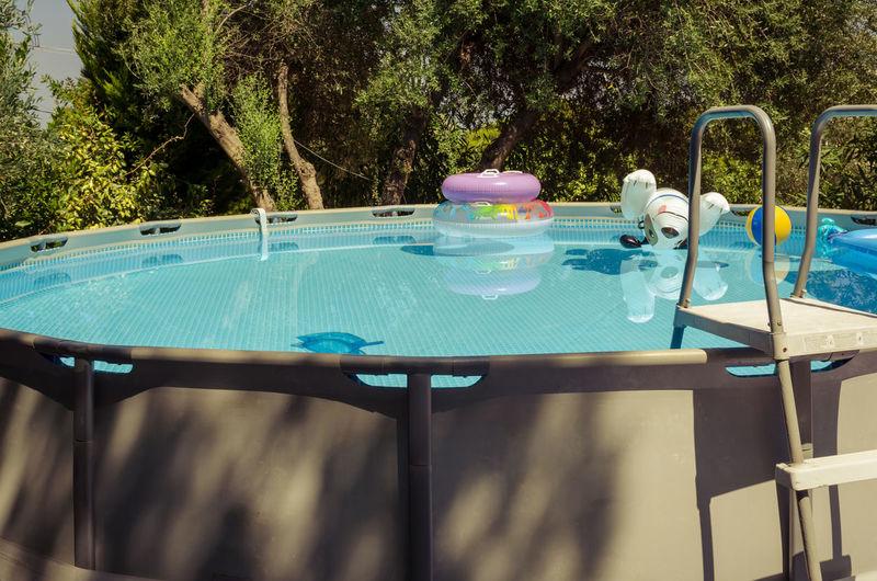 Seasonal swimming pool Ladder Blue Childhood Day Flotation Ring Nature No People Outdoors Plastic Toys Pool Seasonal Sunlight Swimming Pool Tree Water