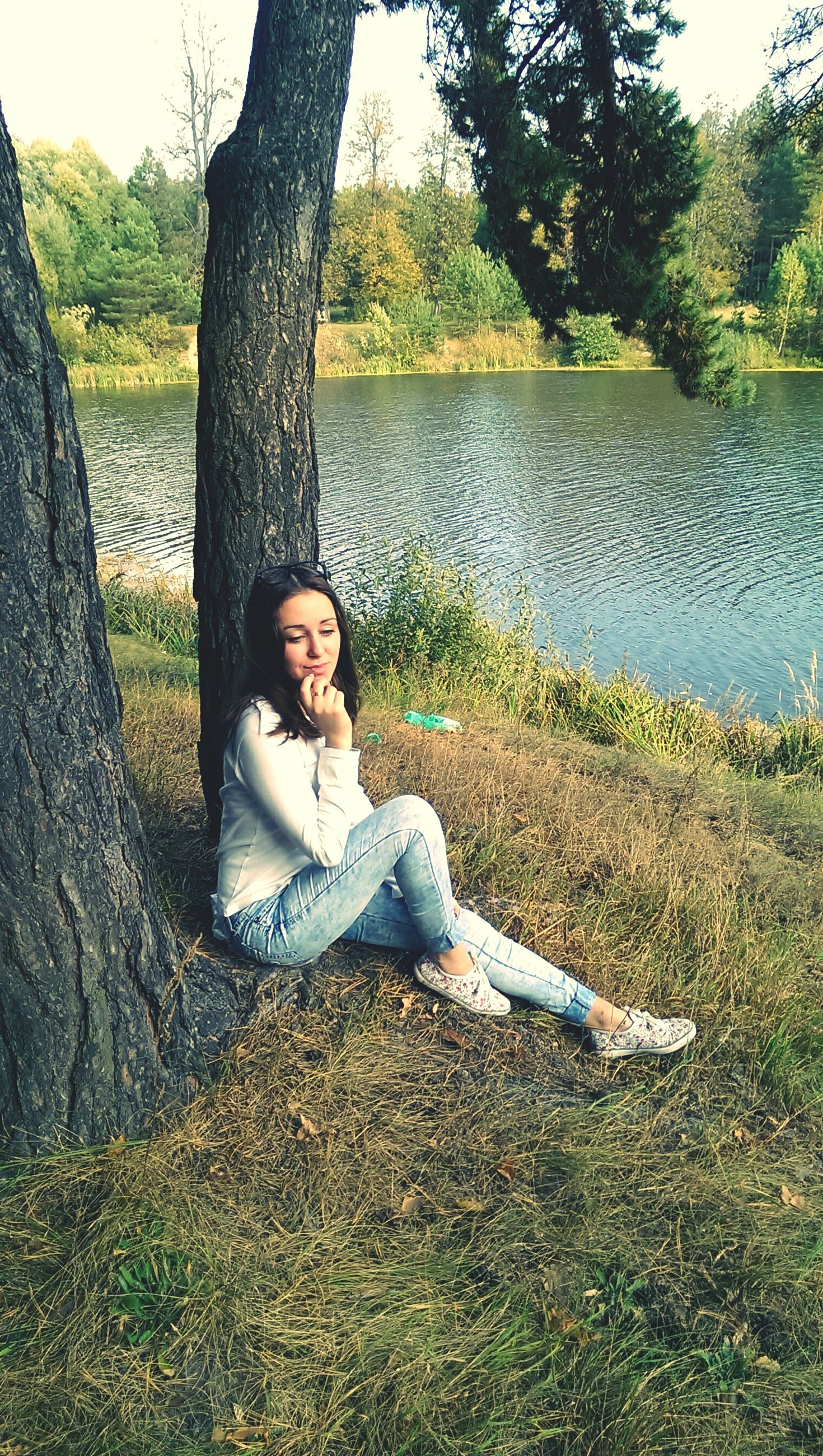 tree, young adult, lifestyles, casual clothing, person, leisure activity, grass, sitting, relaxation, young women, water, standing, full length, nature, day, three quarter length, looking at camera, tranquility