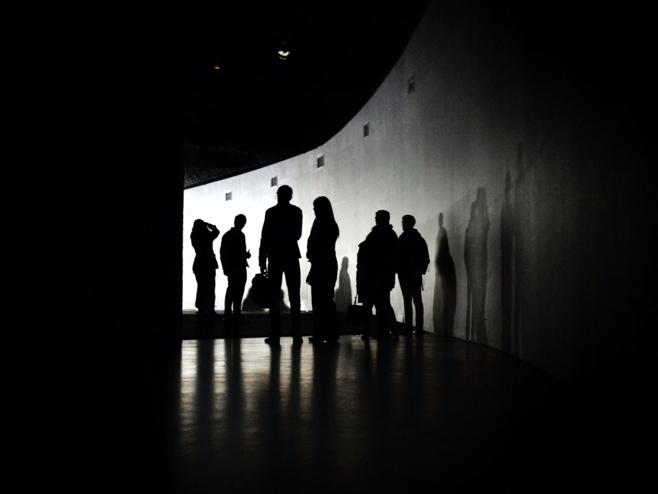 People wait to enter Random International's Rain Room at the Barbican Centre in London