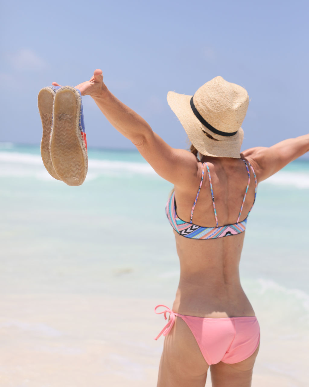 Rear View Of Woman Wearing Bikini While Standing On Shore At Beach