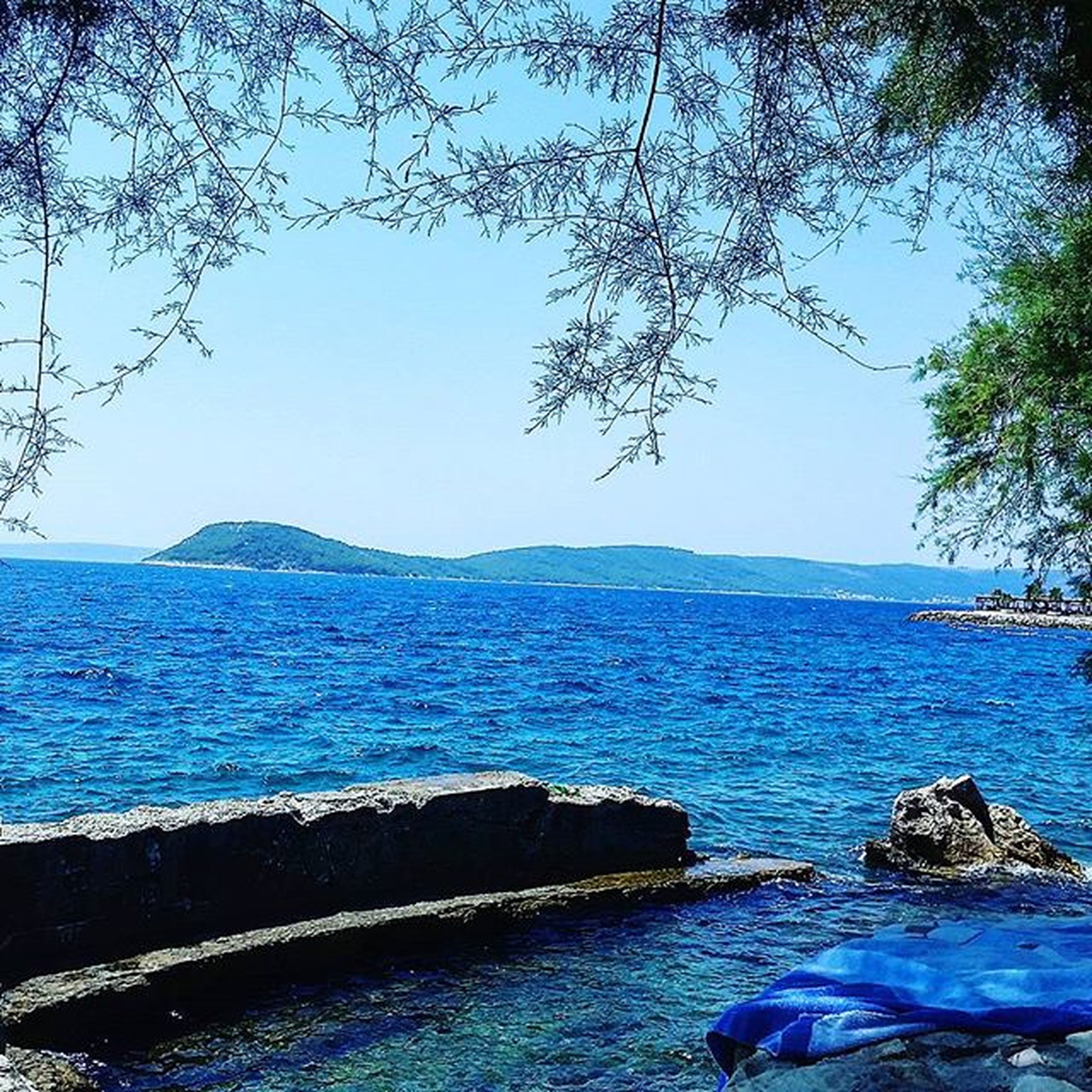 water, sea, blue, tranquil scene, scenics, beauty in nature, tranquility, clear sky, nature, tree, rippled, rock - object, sky, idyllic, day, horizon over water, mountain, outdoors, no people, branch