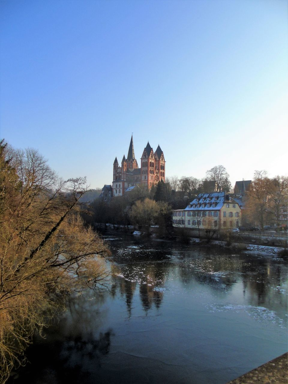 architecture, built structure, river, building exterior, water, no people, bridge - man made structure, outdoors, castle, clear sky, day, tree, nature, city, sky