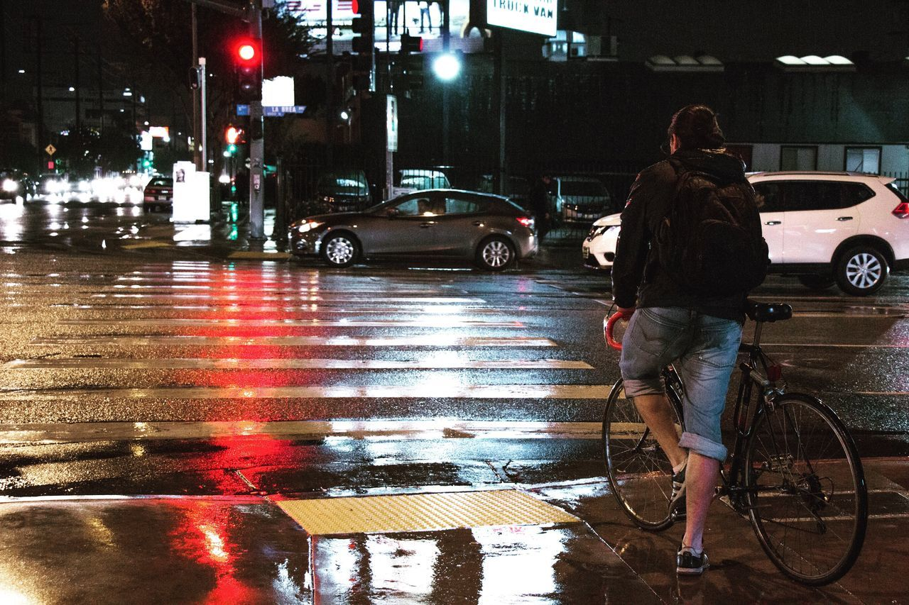 Night Street Transportation City City Street City Life Land Vehicle Mode Of Transport Illuminated Car Full Length Bicycle Rain Real People Outdoors Standing Road Building Exterior One Person Adults Only