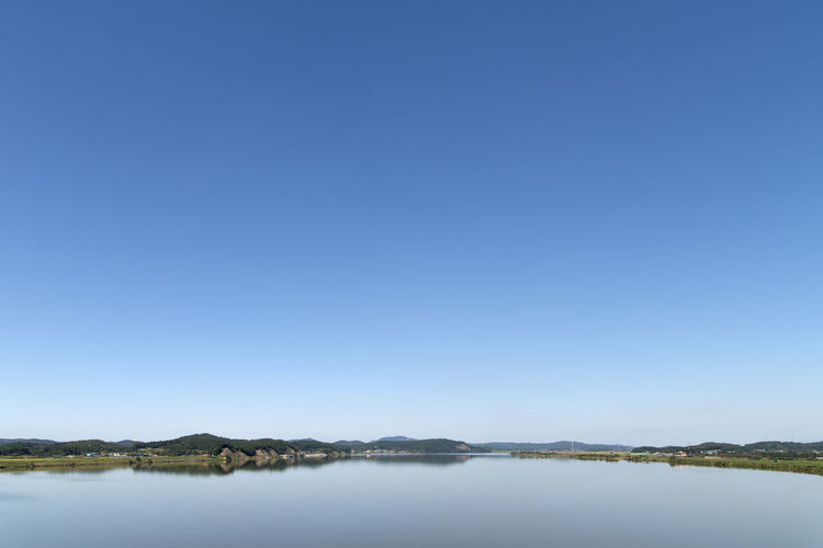 rural landscape at Wungpodaegyo Bridge in Iksan, Jeonbuk, South Korea Geumgang Geumgang River Riverside Beauty In Nature Blue Clear Sky Day Lake Mountain Nature No People Outdoors Rural Landscape Scenics Sky Tranquil Scene Tranquility Tree View Into Land Water Waterfront