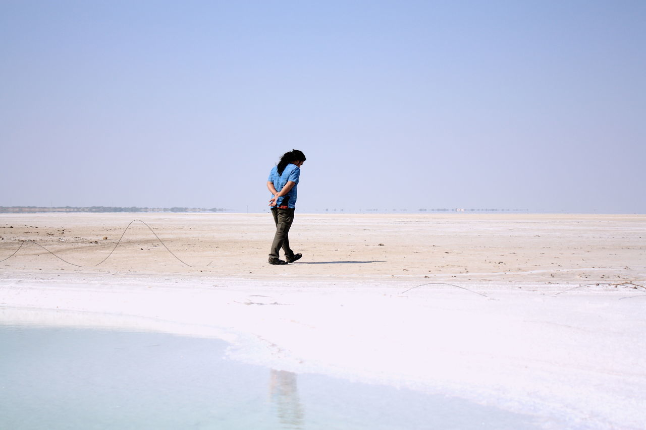 full length, clear sky, beach, real people, nature, salt flat, salt basin, water, copy space, sand, scenics, beauty in nature, day, outdoors, one person, salt - mineral, sea, walking, arid climate, lifestyles, standing, sky, desert, horizon over water, landscape, men