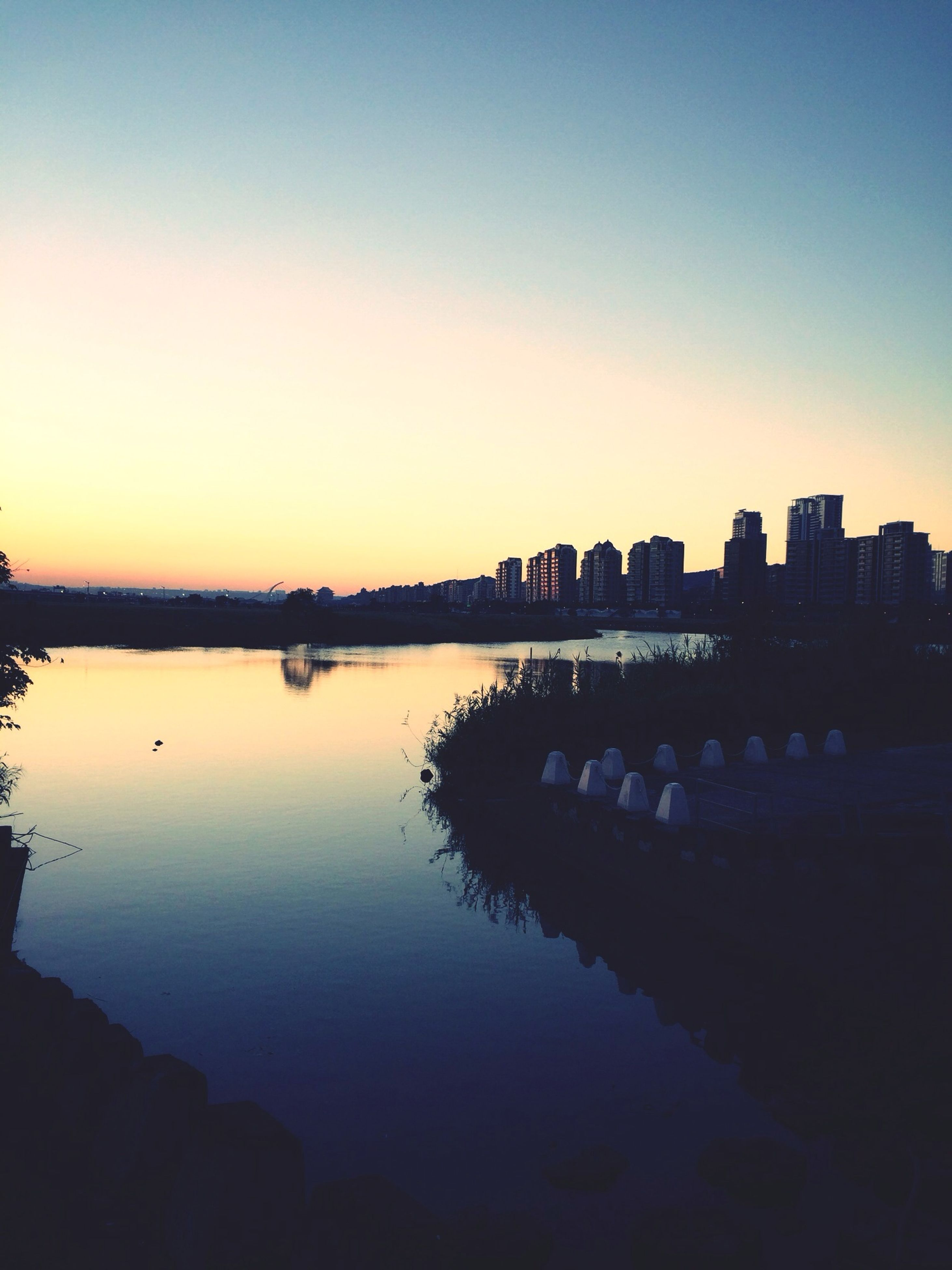 water, silhouette, sunset, clear sky, reflection, copy space, built structure, architecture, building exterior, tranquility, dusk, tranquil scene, river, lake, scenics, nature, standing water, waterfront, beauty in nature, sky