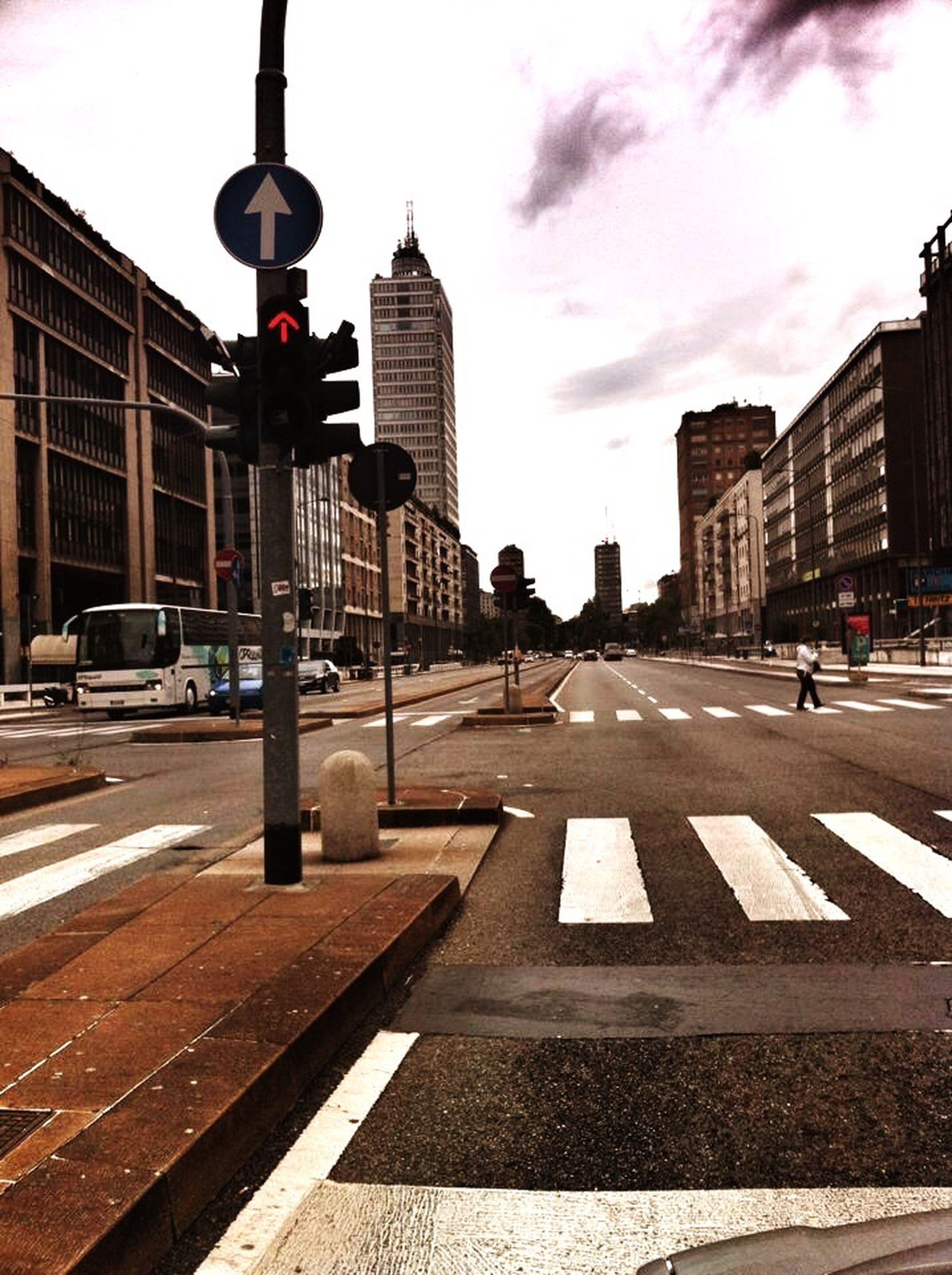 building exterior, architecture, built structure, city, transportation, road marking, street, road, the way forward, arrow symbol, road sign, guidance, sky, car, city life, city street, communication, diminishing perspective, asphalt, incidental people