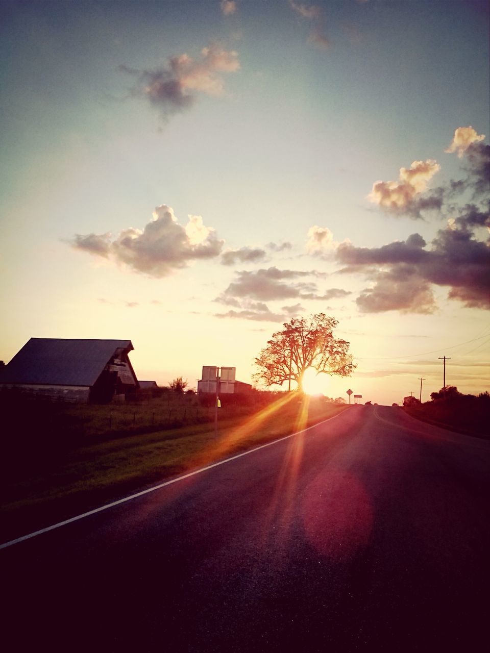 road, sky, street, transportation, sun, sunbeam, sunset, the way forward, car, lens flare, sunlight, no people, house, outdoors, silhouette, built structure, cloud - sky, nature, scenics, day, building exterior, architecture, tree