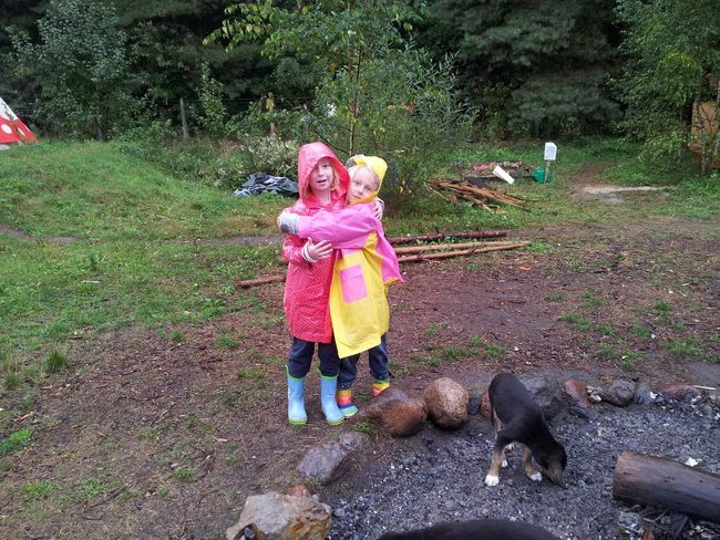 Two girls hugging each other during a camp Camping Childhood Country Elementary Age Girls Hugging Leisure Activity Lifestyles Raincoats Rainy Weather School Trip Survival Together Two Girls Village Wellingtone Yellow