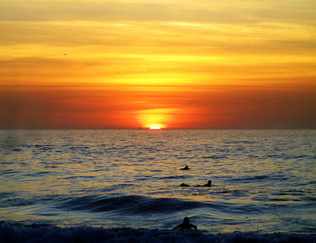 Atmosphere Atmospheric Mood Beauty In Nature Distant Dramatic Sky Horizon Over Water Idyllic Light Majestic Moody Sky Orange Color Outdoors Scenics Sea Silhouette Sky Sun Sunrise Tranquil Scene Water Swimmer