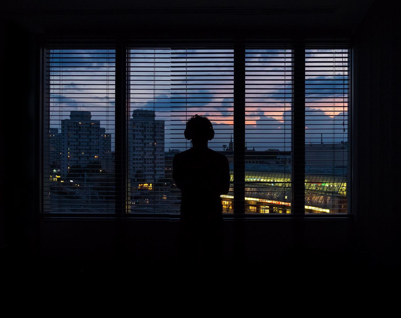window, silhouette, indoors, rear view, skyscraper, cityscape, looking through window, real people, one person, looking at view, sky, men, city, standing, sunset, lifestyles, architecture, day, urban skyline, people