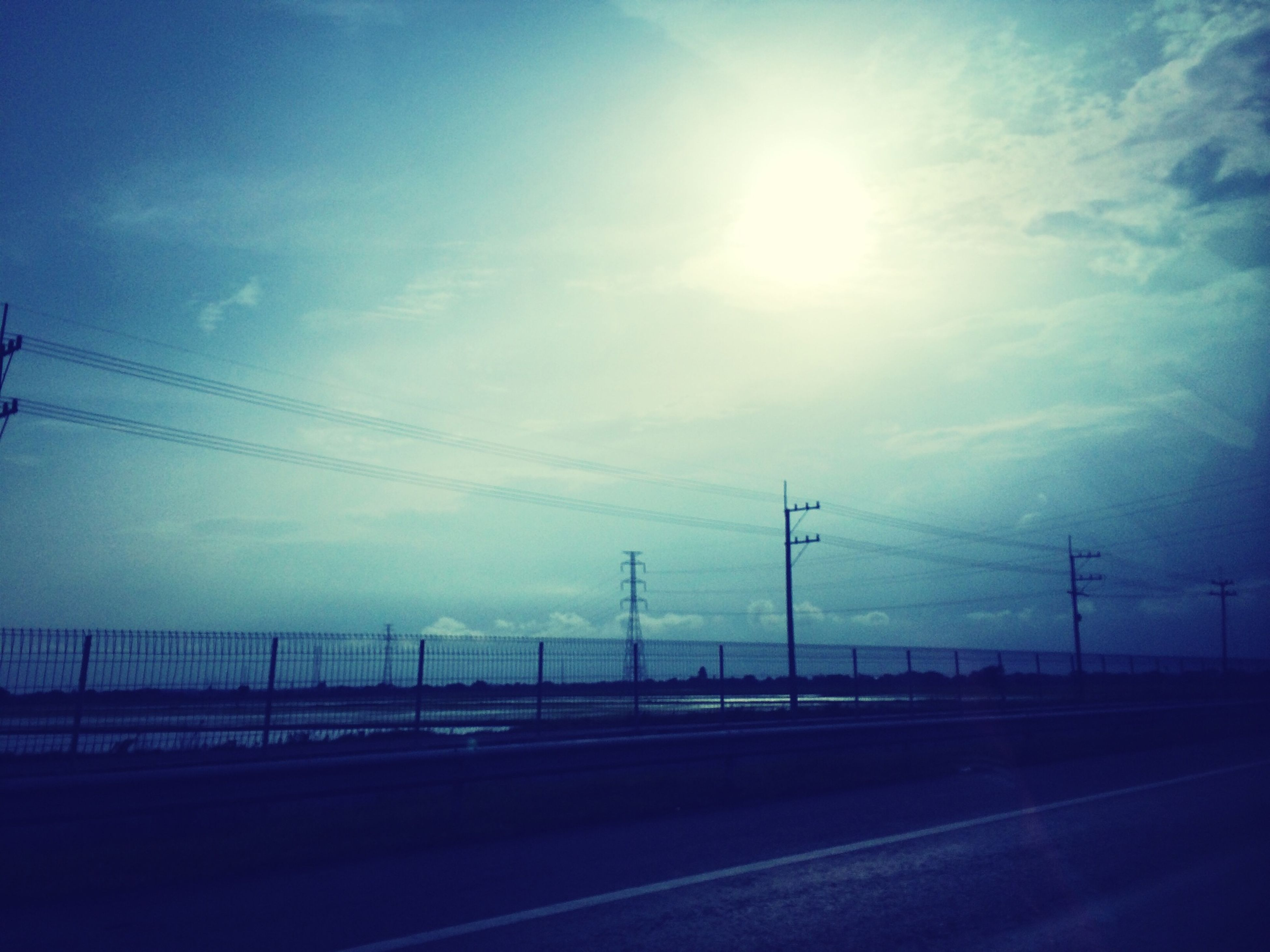 electricity pylon, power line, connection, sky, electricity, power supply, transportation, fuel and power generation, road, cable, sun, cloud - sky, sunlight, landscape, tranquility, nature, sunbeam, silhouette, technology, tranquil scene