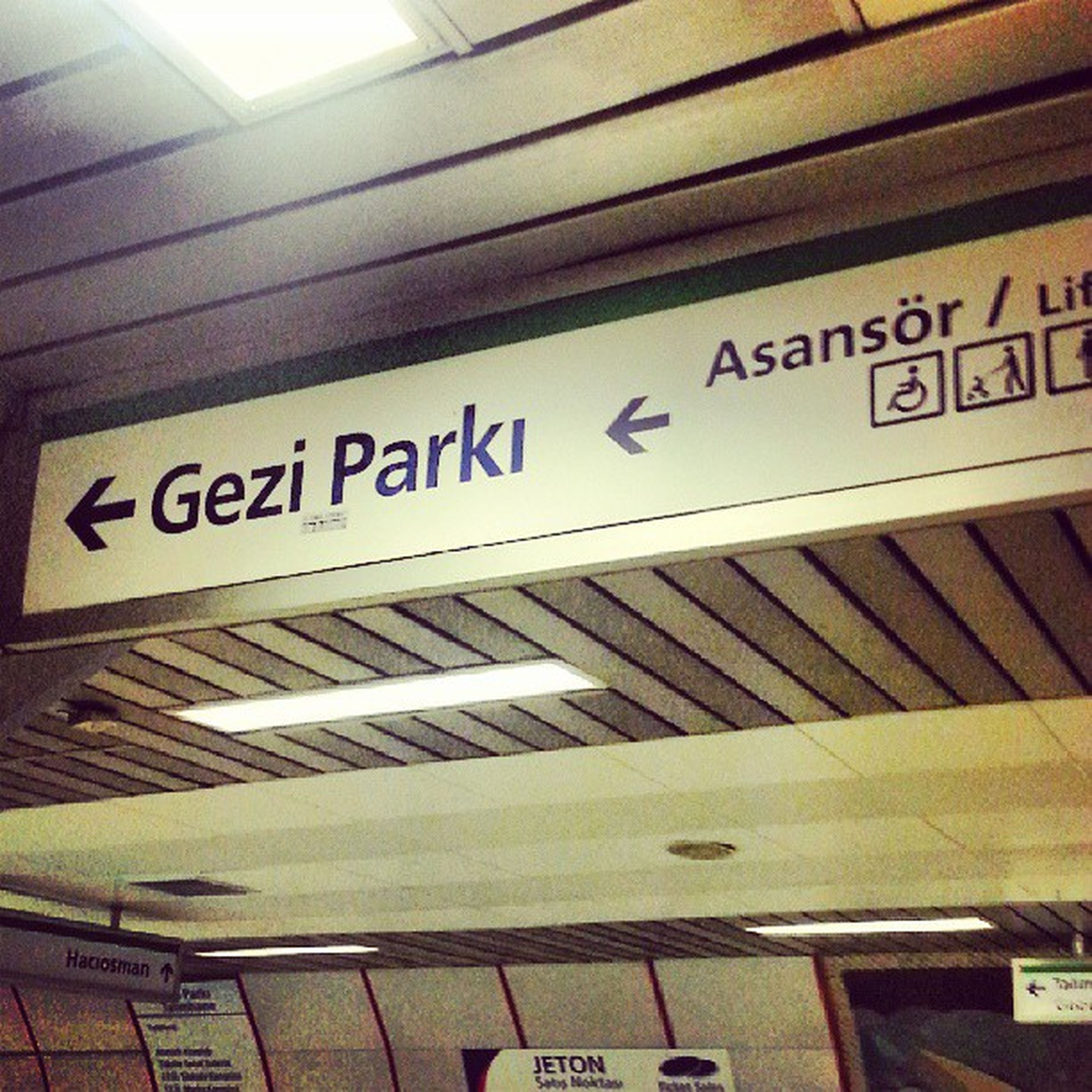 text, western script, communication, indoors, non-western script, information sign, low angle view, information, architecture, capital letter, built structure, sign, railroad station, number, no people, subway station, ceiling, public transportation, arrow symbol, guidance