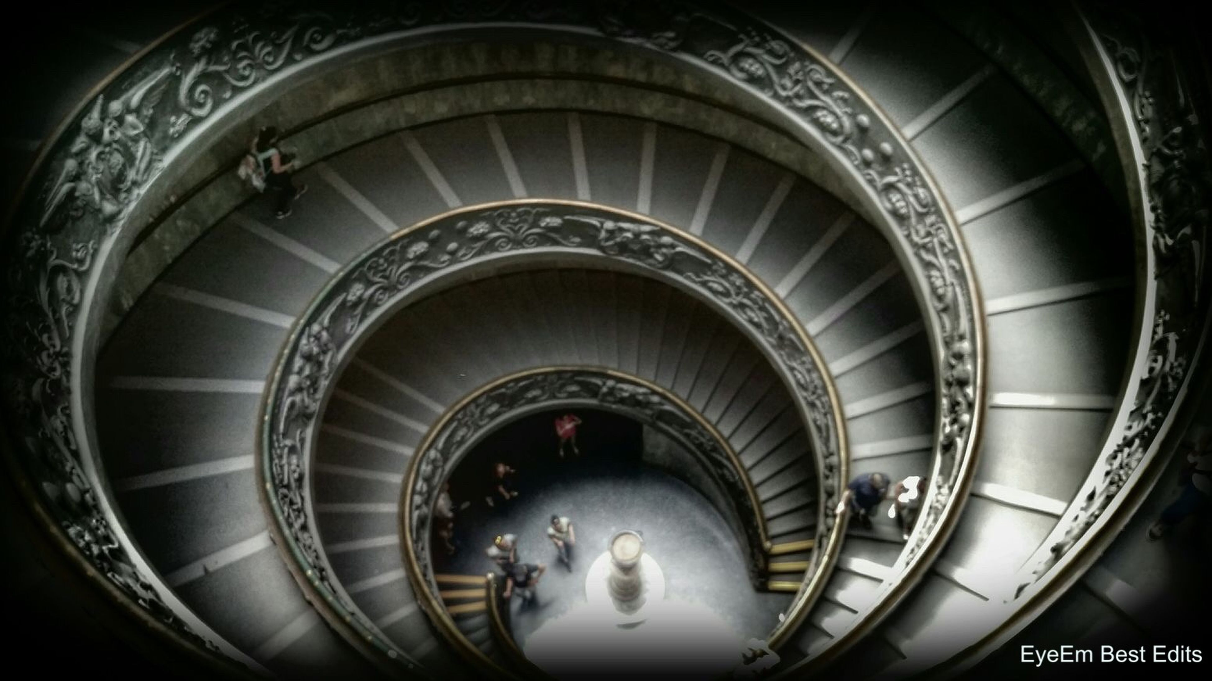 indoors, steps, steps and staircases, staircase, railing, spiral staircase, spiral, built structure, architecture, high angle view, low angle view, ceiling, escalator, arch, tunnel, pattern, men, travel, circle