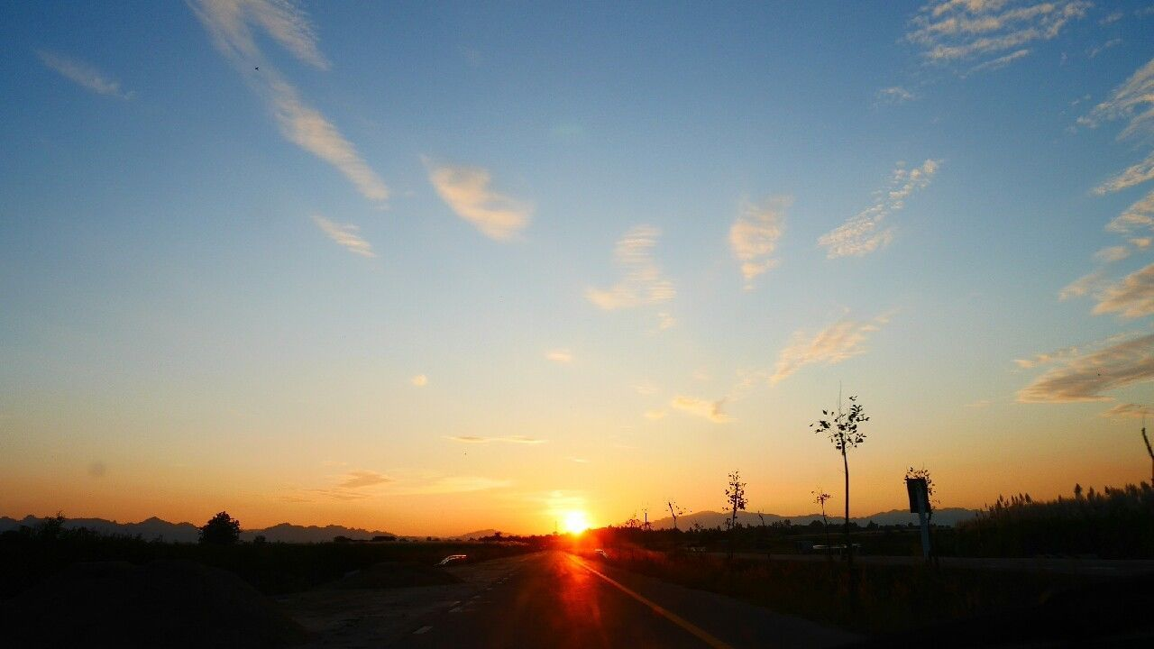 sunset, sky, road, orange color, silhouette, transportation, cloud - sky, scenics, the way forward, tranquil scene, sun, nature, outdoors, beauty in nature, tree, no people, day