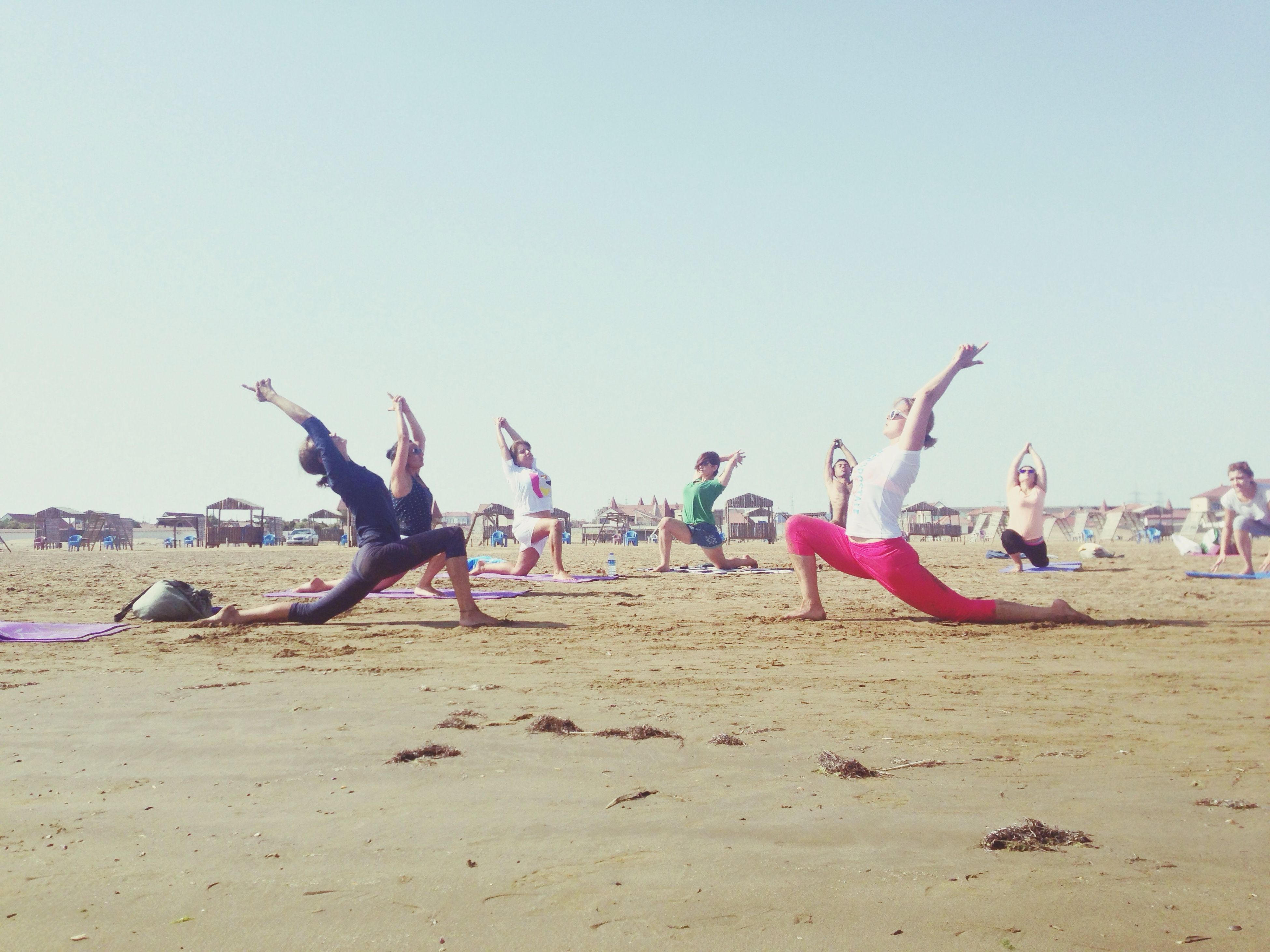 beach, sand, leisure activity, clear sky, lifestyles, large group of people, enjoyment, men, copy space, fun, vacations, shore, sea, person, full length, day, mid-air, tourist, outdoors