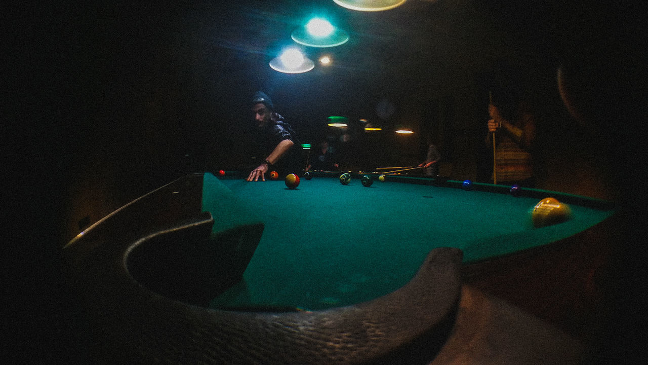 leisure activity, pool table, real people, night, pool ball, playing, ball, enjoyment, fun, skill, pool - cue sport, sport, lifestyles, illuminated, indoors, men, snooker, one person, pool cue, people