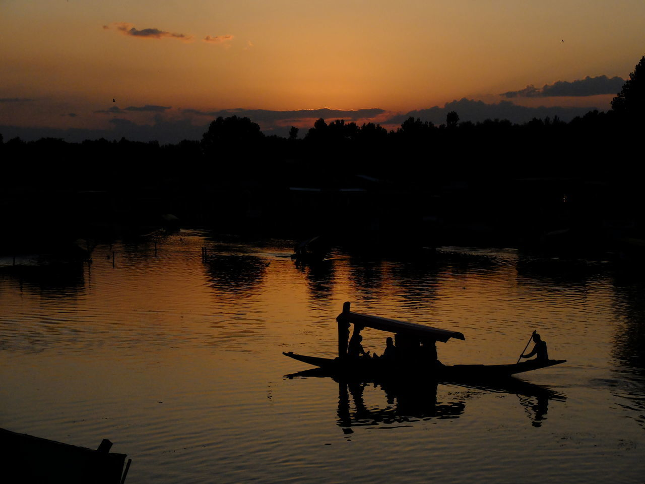 sunset, silhouette, water, nature, reflection, orange color, beauty in nature, outdoors, scenics, lake, tranquility, real people, sky, tree, waterfront, nautical vessel, men, two people, oar, rowing, day, people