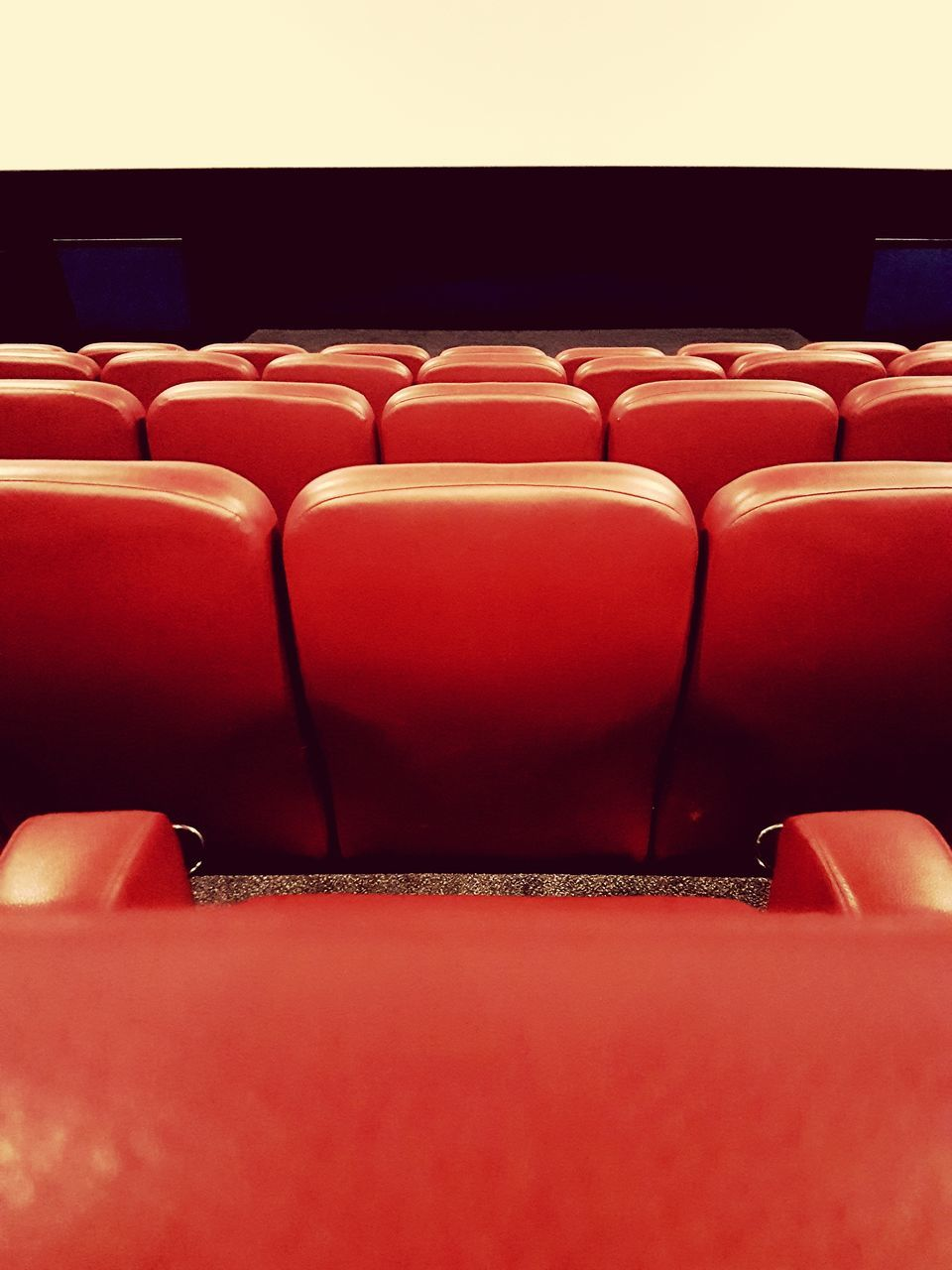 in a row, empty, seat, red, indoors, absence, arts culture and entertainment, chair, no people, movie theater, auditorium, backgrounds, film industry, day