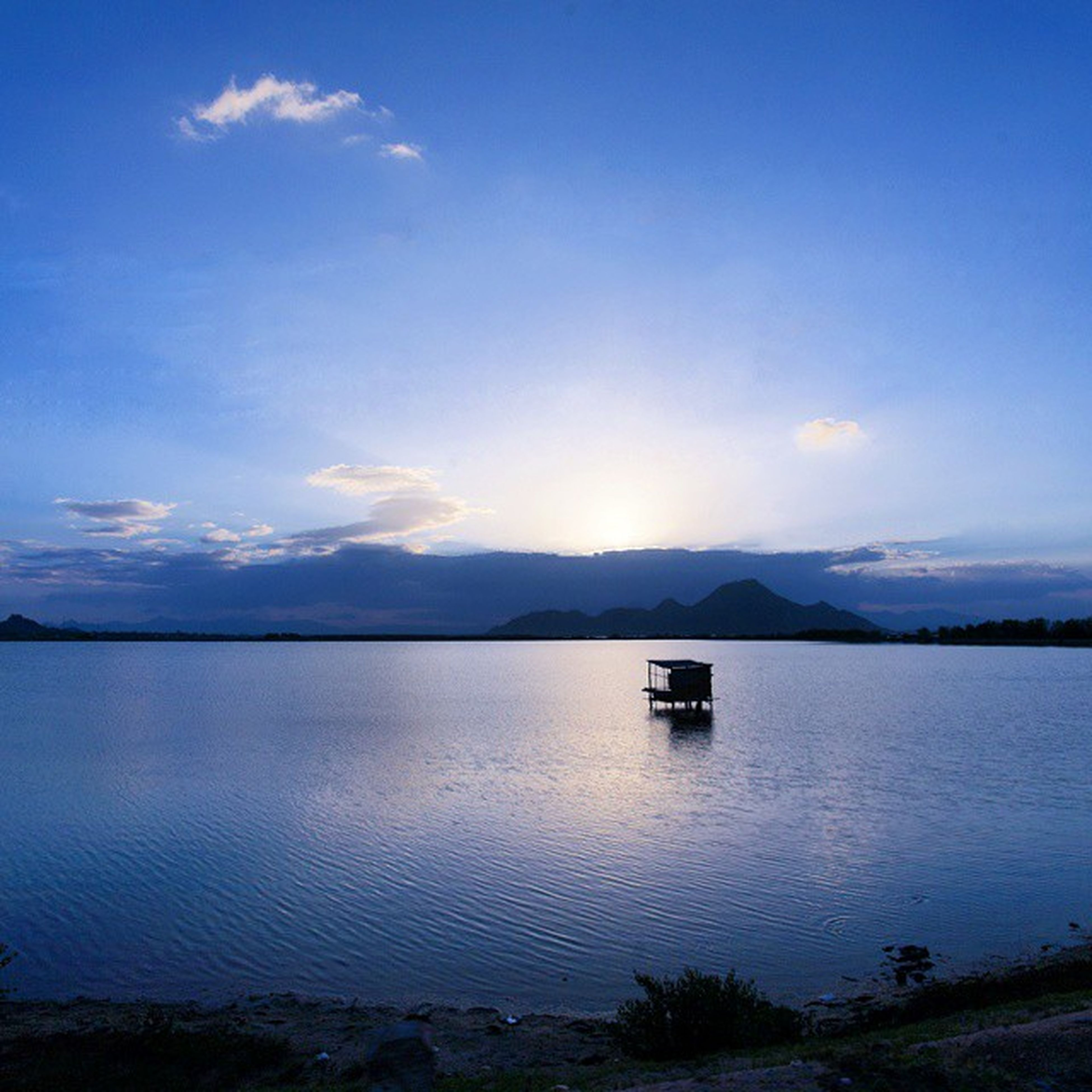 water, tranquil scene, tranquility, scenics, lake, mountain, sky, beauty in nature, reflection, blue, nature, mountain range, calm, idyllic, cloud, waterfront, non-urban scene, cloud - sky, outdoors, no people