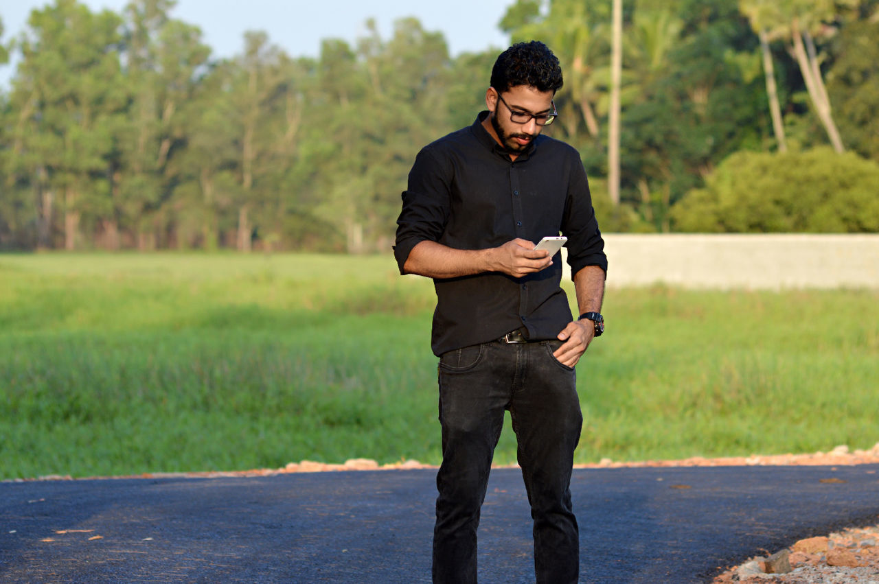 wireless technology, portable information device, one person, smart phone, real people, outdoors, mobile phone, communication, front view, standing, nature, technology, using phone, road, day, lifestyles, young adult, tree, people