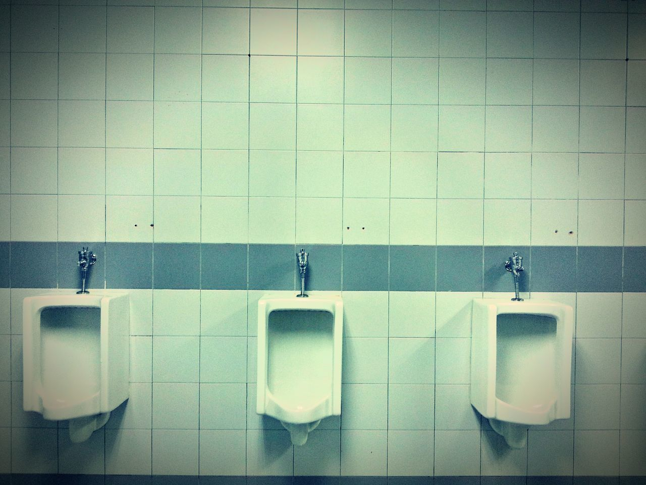 urinal, public building, public restroom, indoors, bathroom, in a row, tile, urgency, repetition, convenience, hygiene, no people, day, flushing toilet