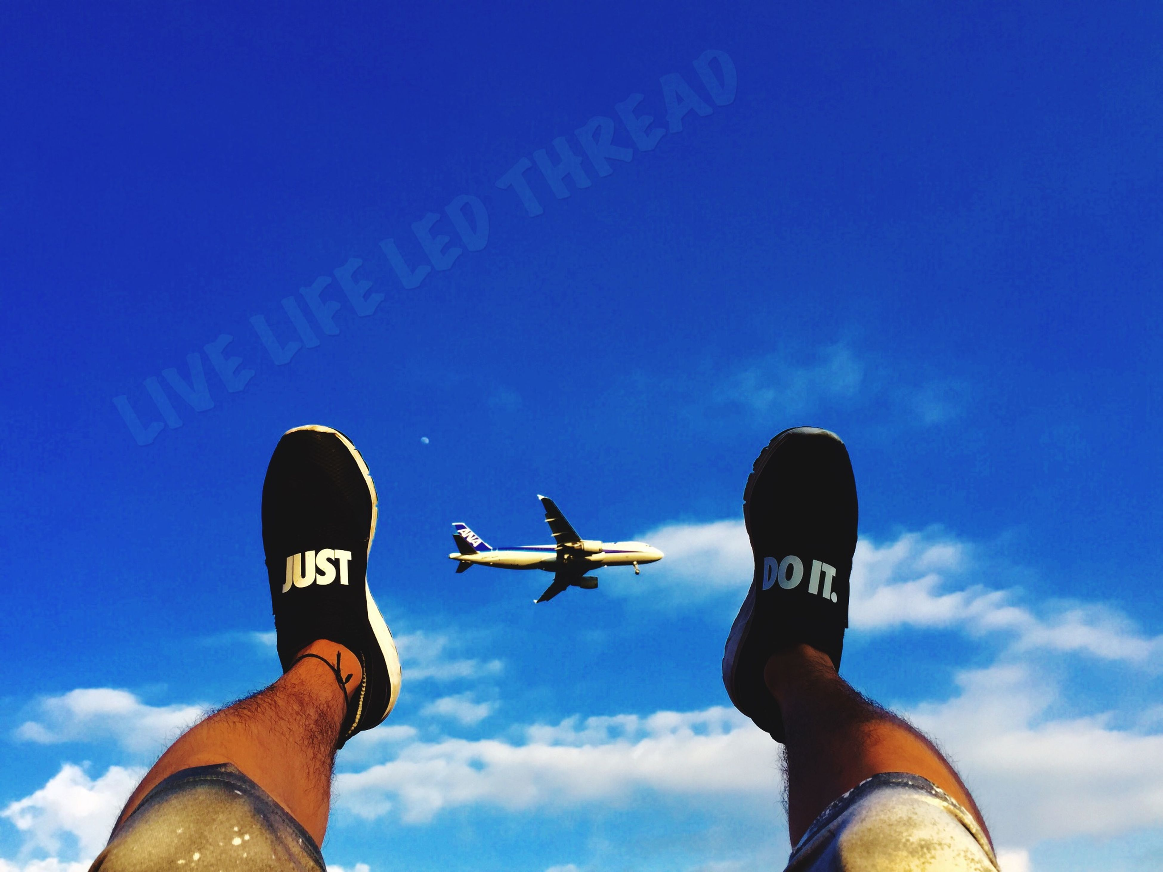 low angle view, personal perspective, person, blue, part of, sky, communication, lifestyles, men, leisure activity, unrecognizable person, holding, cloud - sky, text, cropped, guidance, human finger