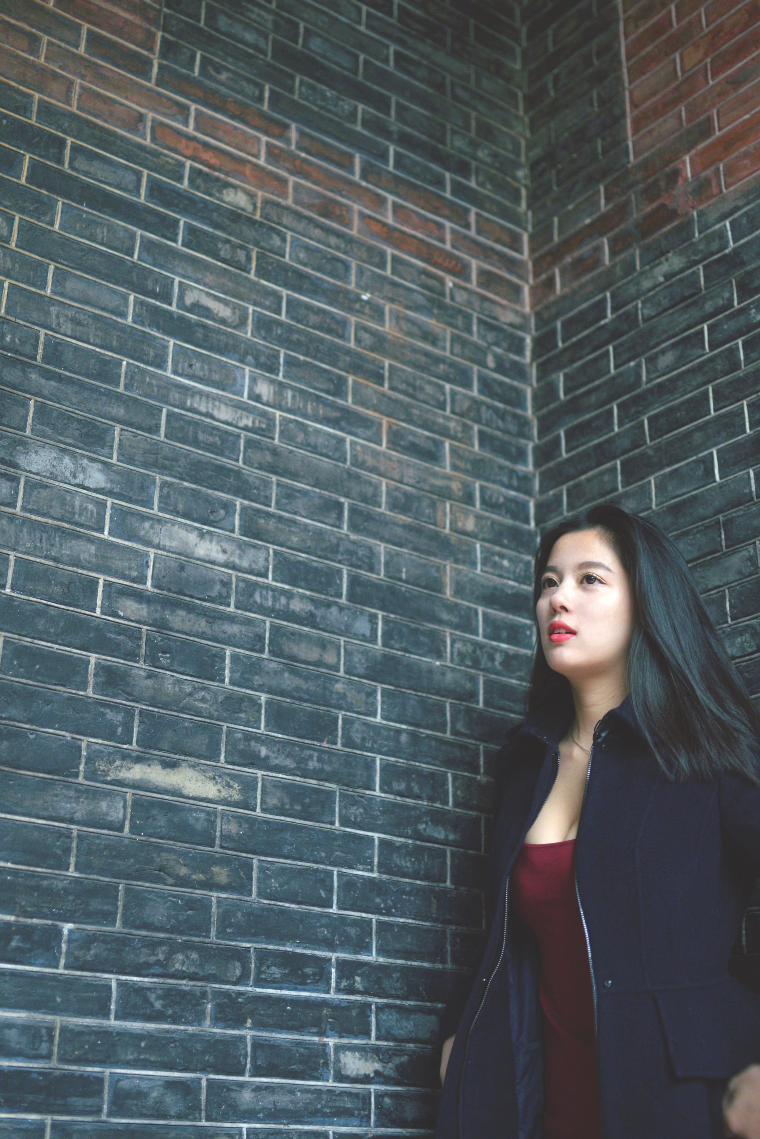 young adult, looking at camera, lifestyles, portrait, front view, person, casual clothing, young women, standing, leisure activity, wall - building feature, brick wall, architecture, built structure, smiling, wall, building exterior