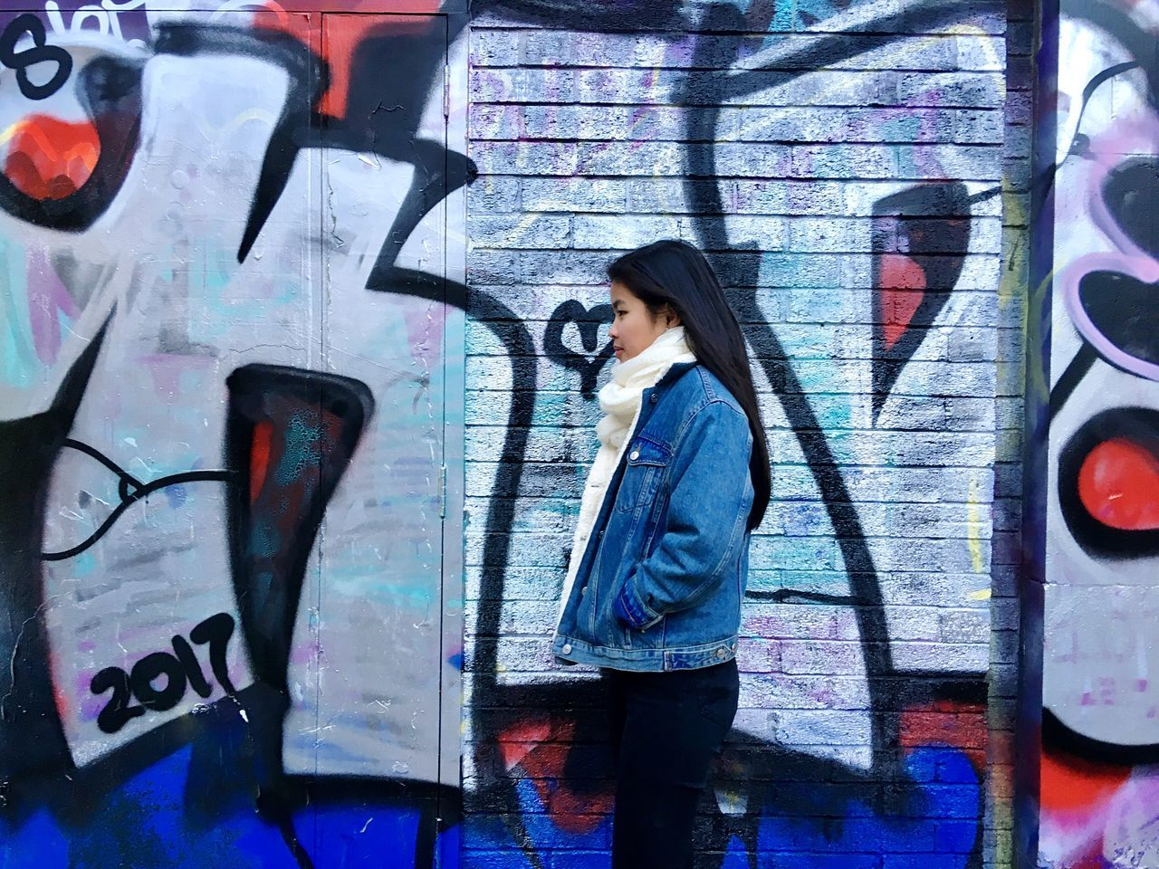 graffiti, one person, young adult, casual clothing, real people, black hair, street art, lifestyles, leisure activity, young women, standing, multi colored, side view, outdoors, day, one young woman only, adult, people, adults only