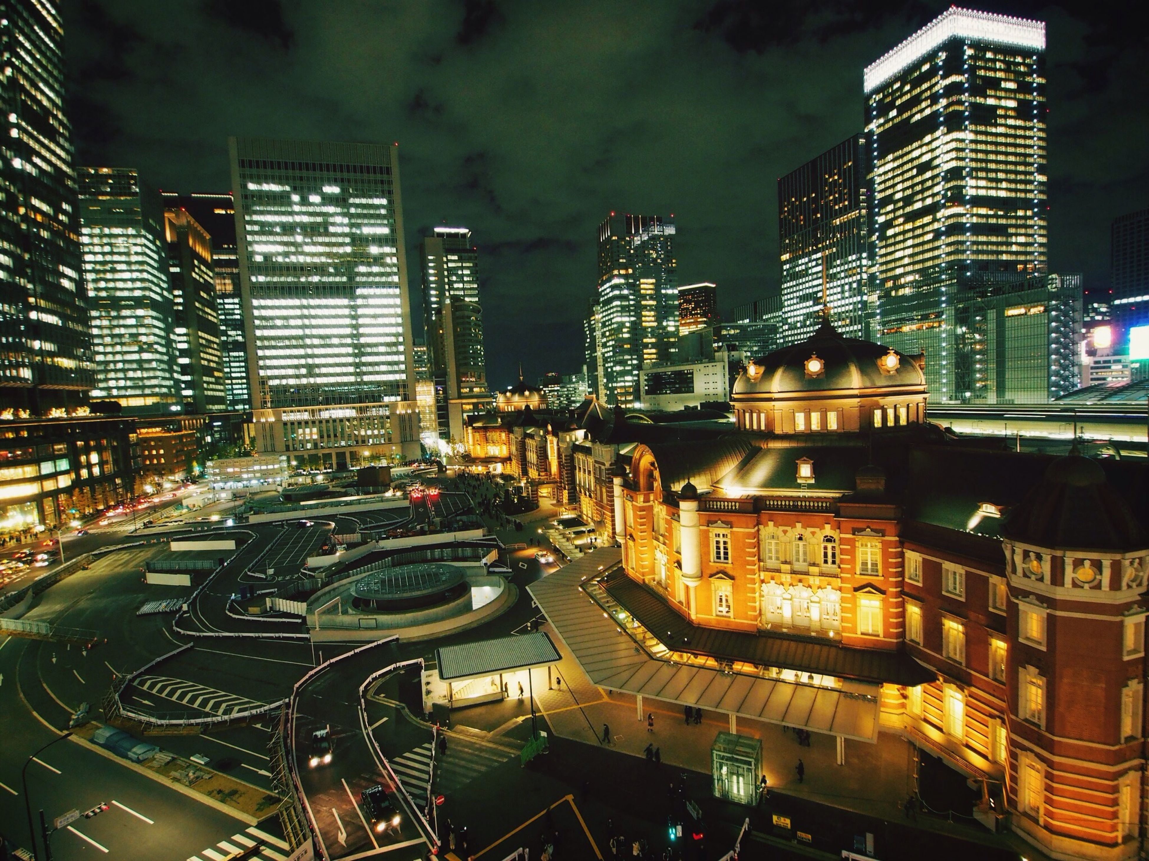 building exterior, city, architecture, built structure, illuminated, skyscraper, night, transportation, cityscape, car, city life, office building, tall - high, street, land vehicle, modern, high angle view, city street, traffic, tower