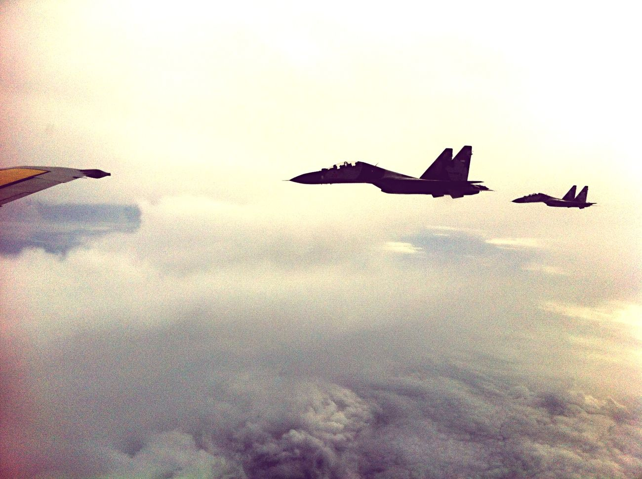 Indonesia Air Force escorted by two Sukhoi_an airplane window_