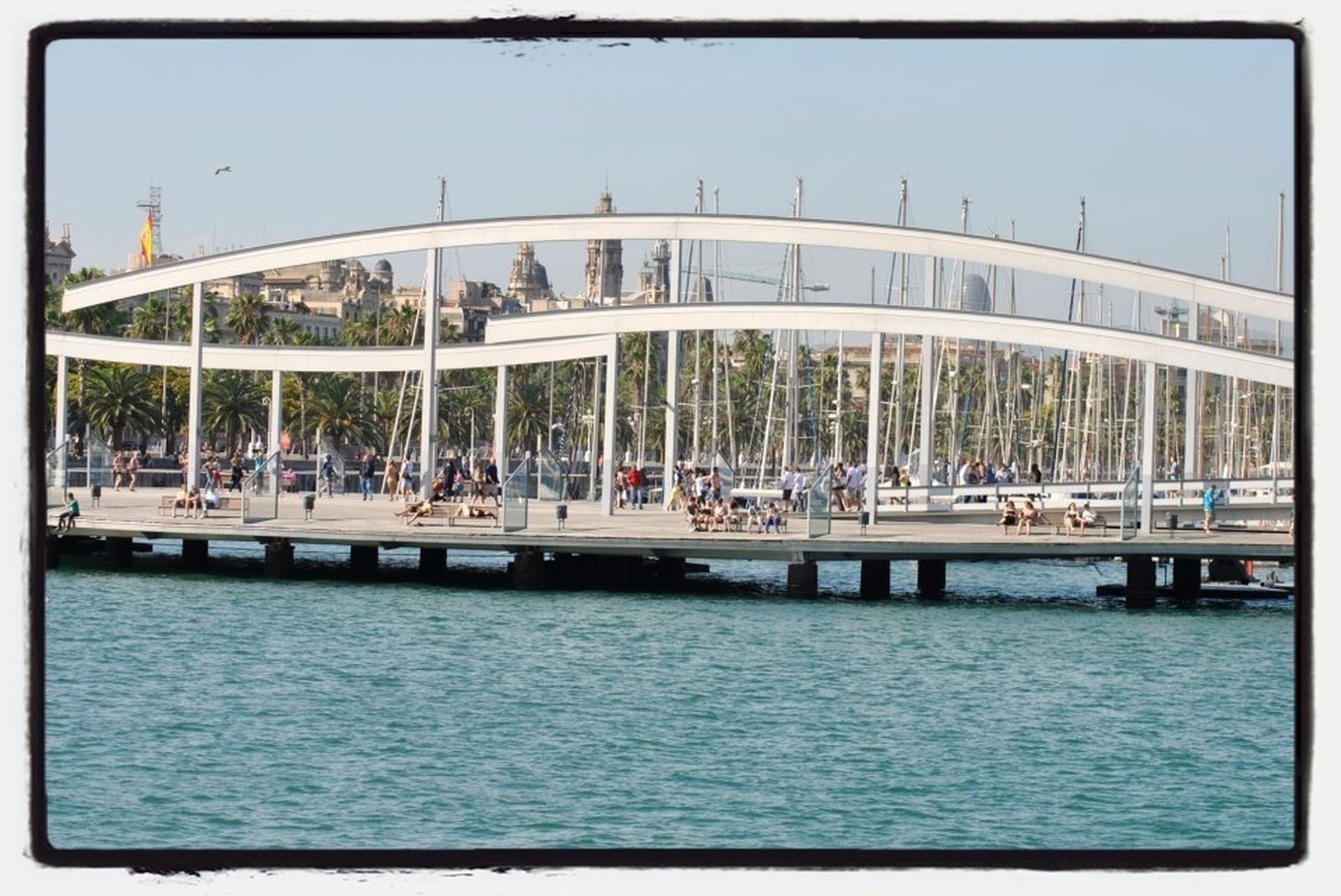 transfer print, water, auto post production filter, built structure, waterfront, architecture, transportation, river, nautical vessel, large group of people, day, building exterior, boat, incidental people, mode of transport, in a row, outdoors, reflection, sea, city