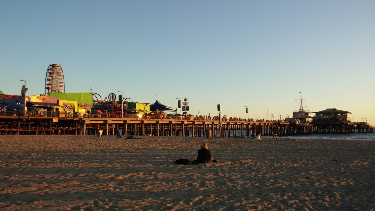 beach, clear sky, sand, built structure, leisure activity, outdoors, architecture, building exterior, nature, real people, day, sitting, sky, sea, water, animal themes, one person, carousel, people