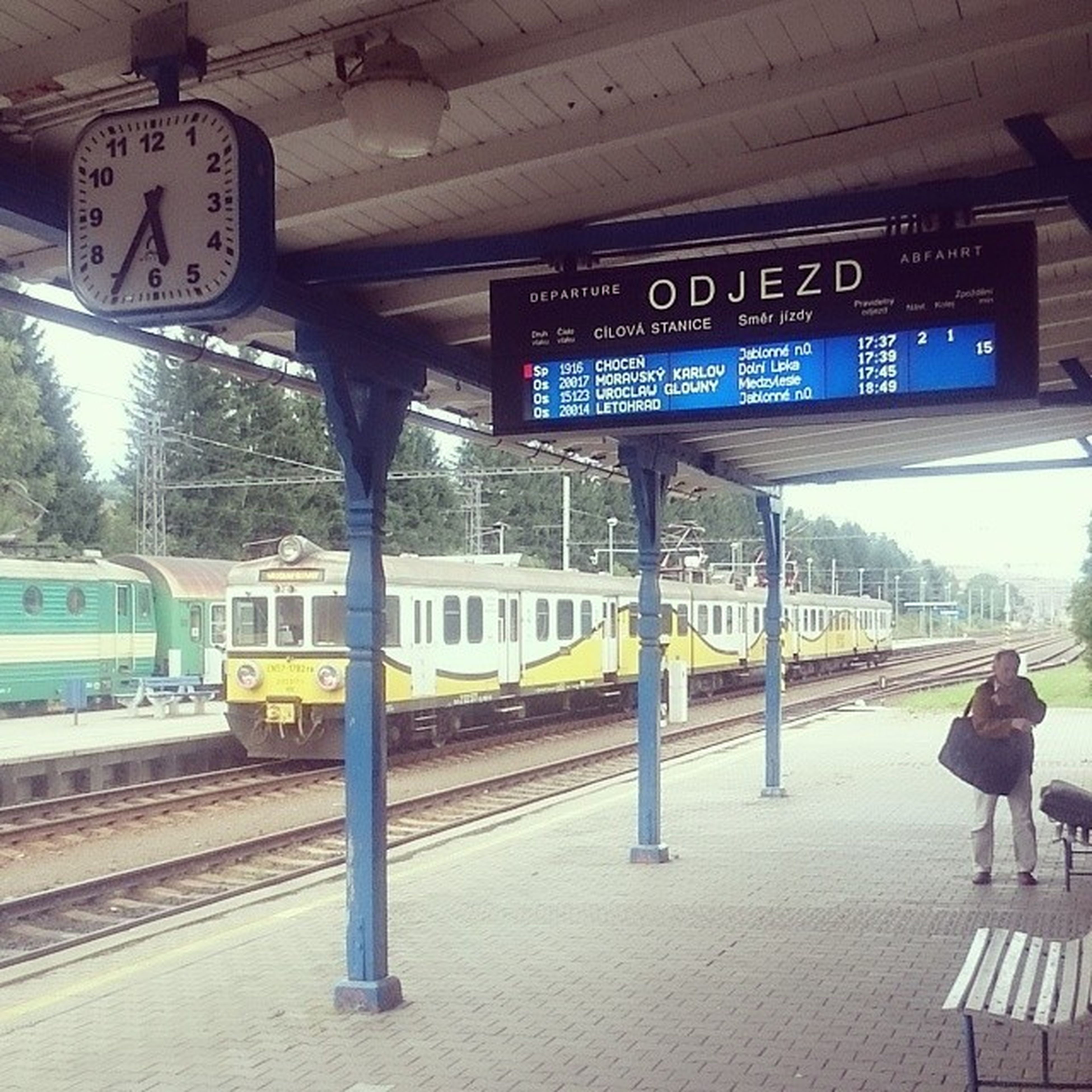 transportation, railroad station, railroad station platform, public transportation, text, rail transportation, architecture, western script, built structure, travel, railroad track, train - vehicle, communication, mode of transport, incidental people, information sign, men, non-western script, indoors