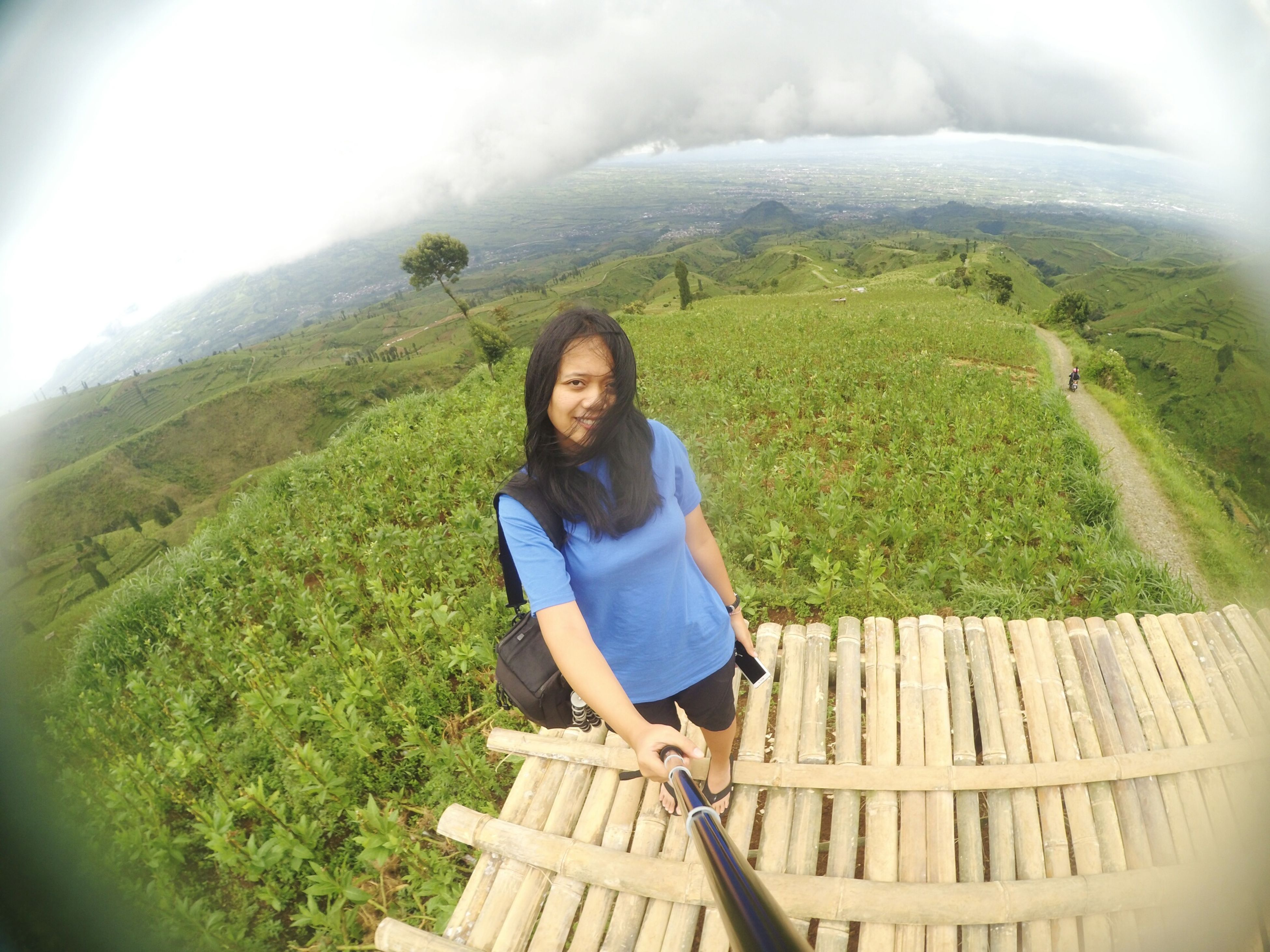 mountain, young adult, young women, leisure activity, lifestyles, travel, person, portrait, looking at camera, casual clothing, smiling, scenics, beauty in nature, beauty, tourism, vacations, nature, journey, tourist, cloud - sky, tranquil scene, mountain range, tranquility, majestic, weekend activities, non-urban scene, green color