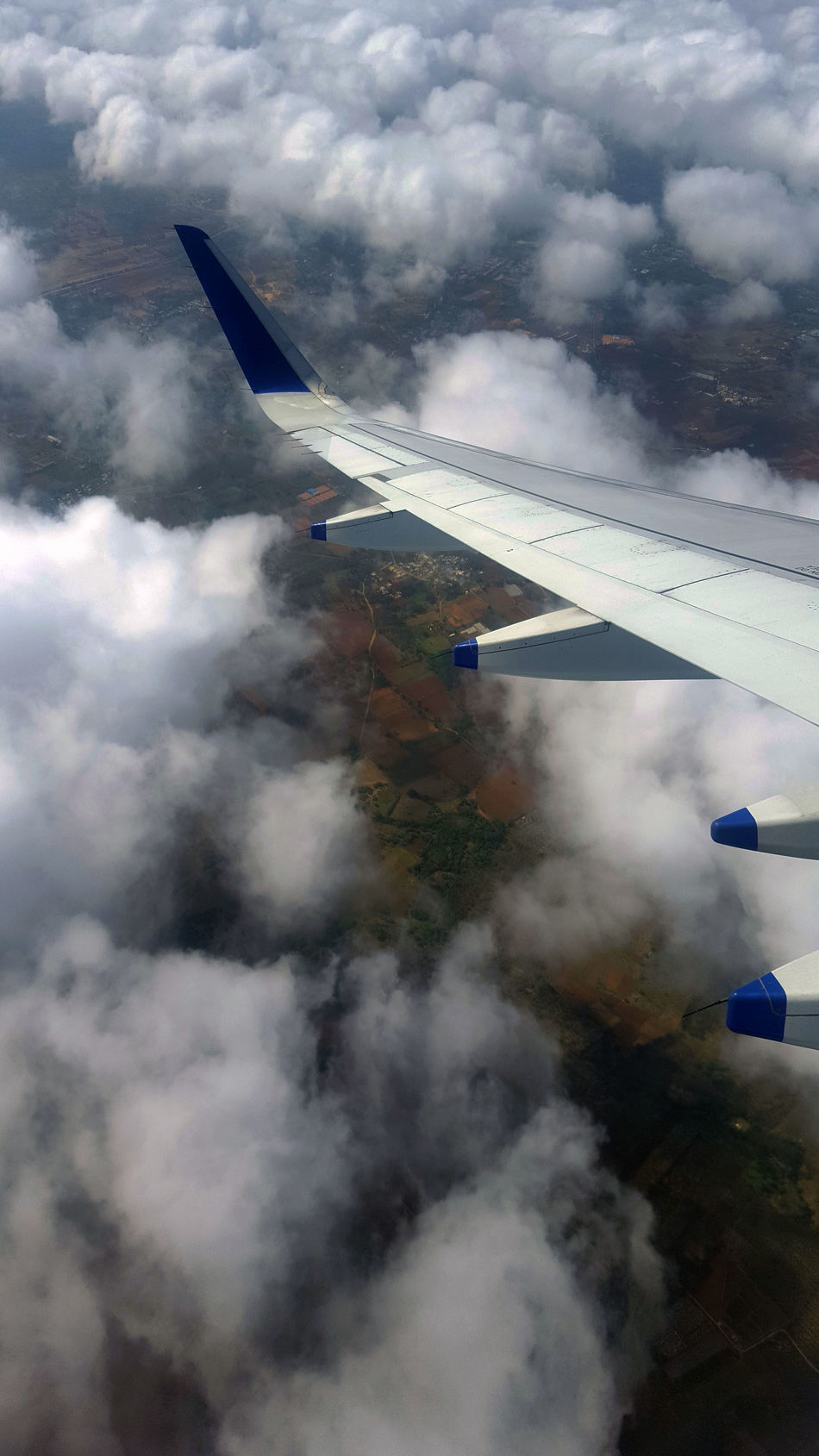 Patches Of Clouds Flying AirplaneCloud - Sky Transportation Mid-air Aerobatics Aerial View Land. Aircraft Wing