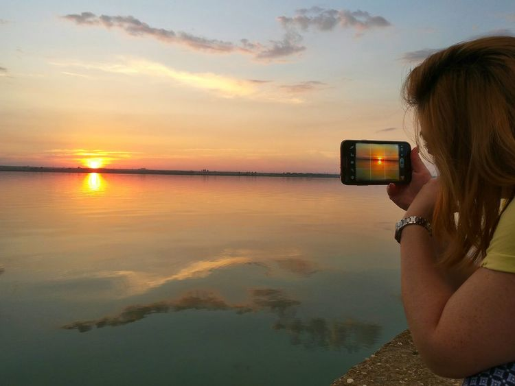 Beautiful Sunset. Taking a Snapshot. The Photographer Sunset Bliss Water Reflections