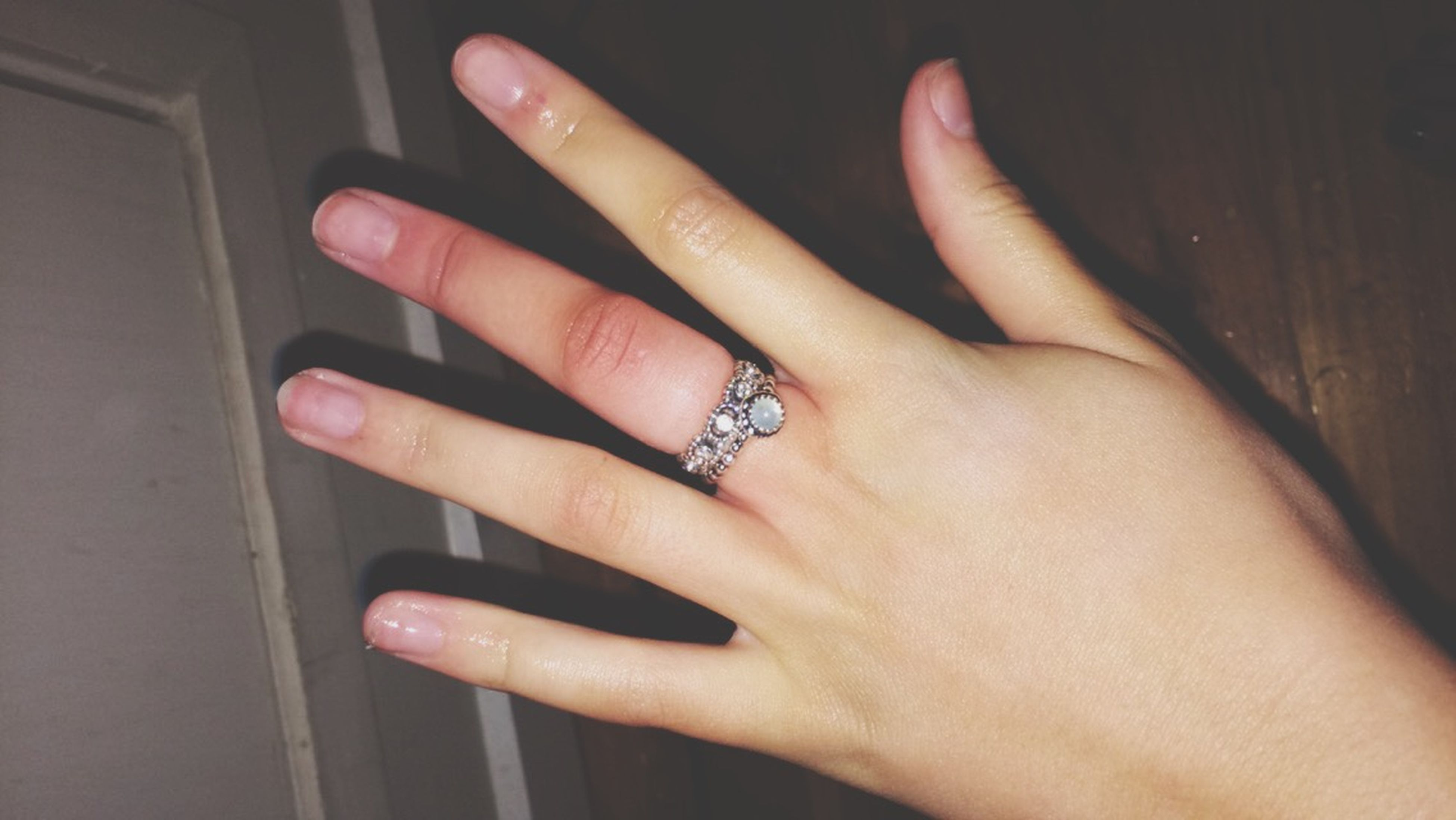 person, indoors, part of, human finger, close-up, holding, cropped, lifestyles, fashion, nail polish, high angle view, unrecognizable person, leisure activity, ring, red, showing