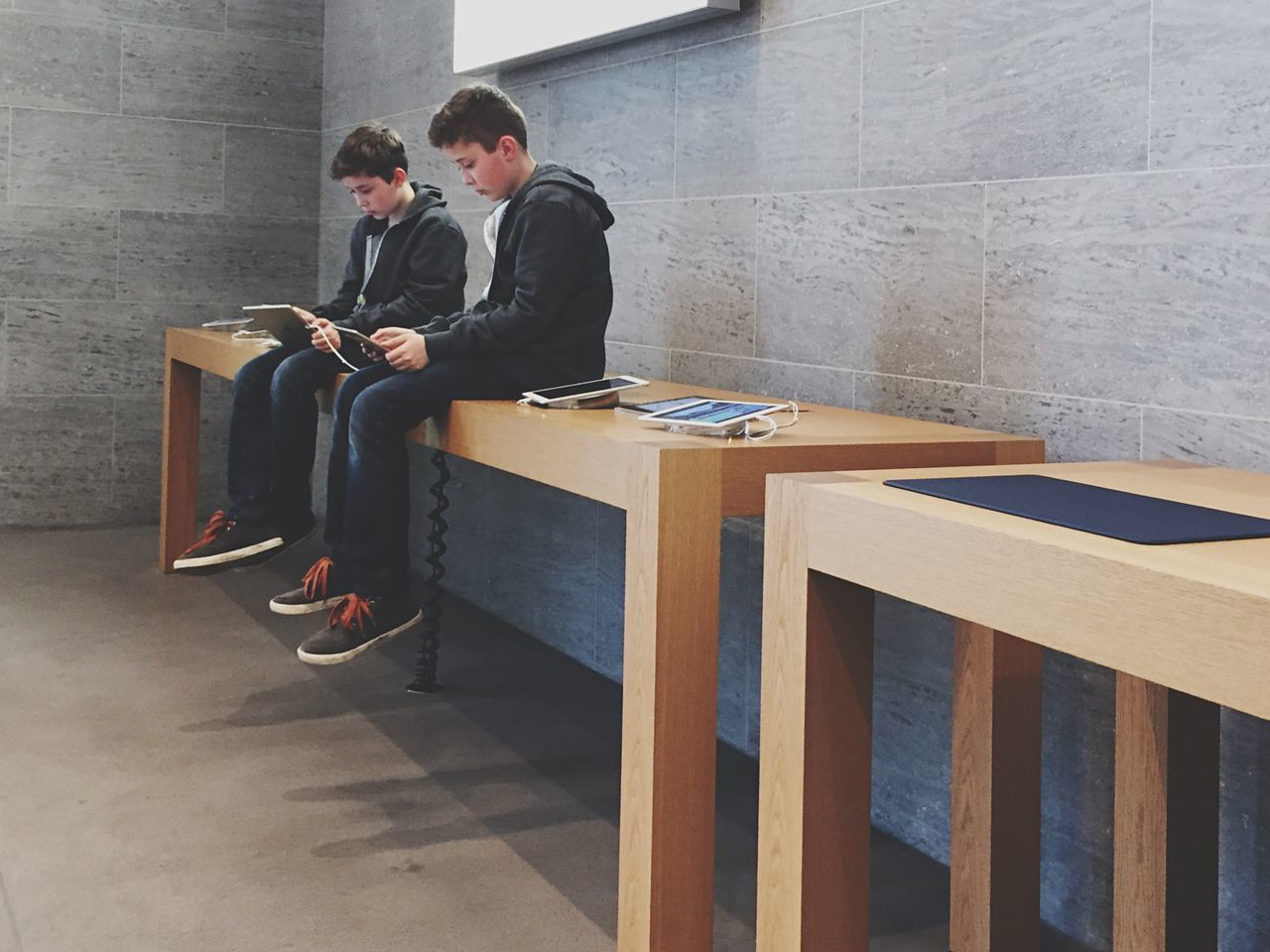 two people, real people, young adult, young men, indoors, sitting, full length, businessman, lifestyles, day, togetherness, men, built structure, boys, young women, architecture, technology, well-dressed, people