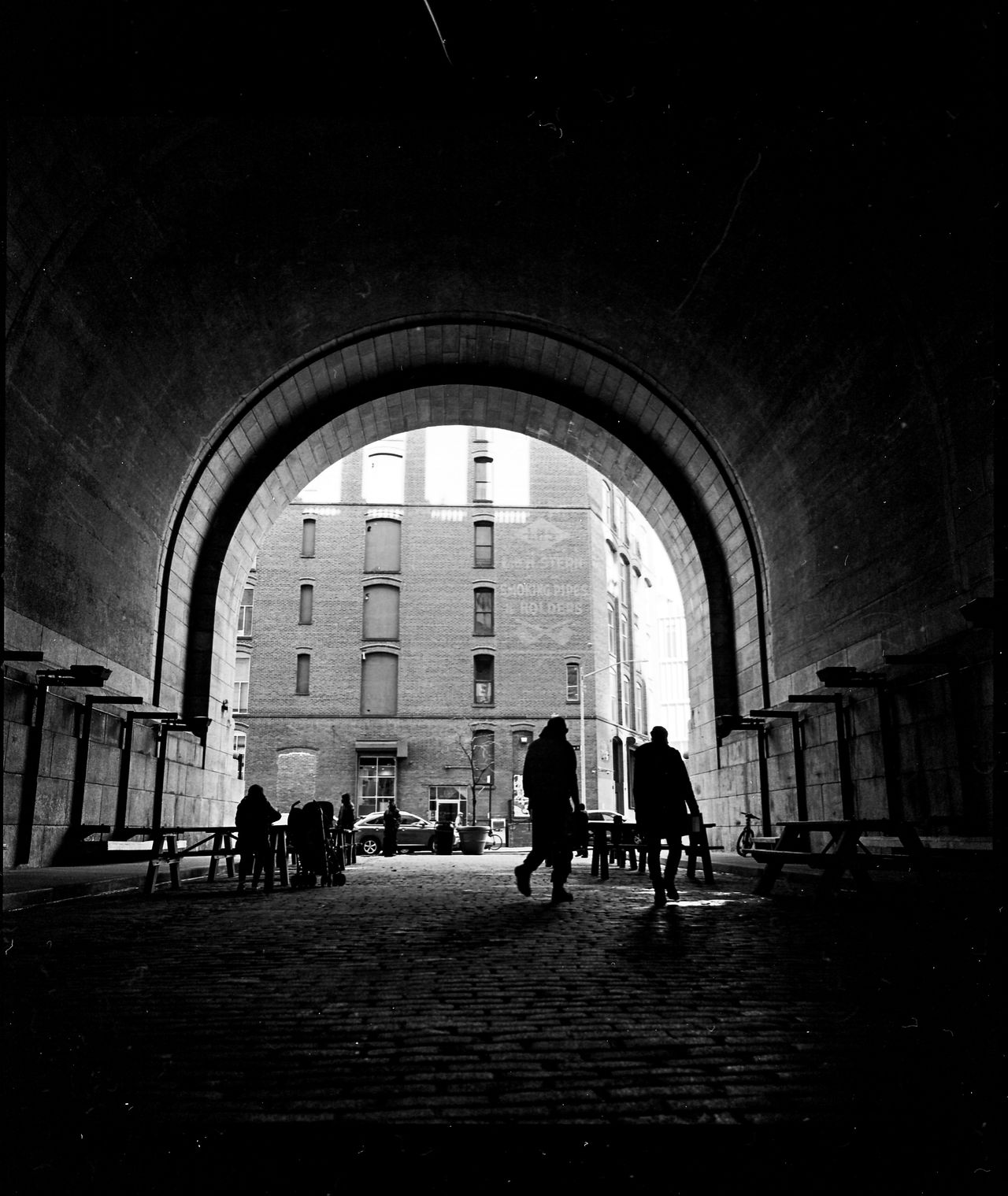 DUMBO with the Hasselblad. Adult Arch Architecture Black & White Building Exterior Built Structure City DUMBO Dumbo Brooklyn DUMBO, Brooklyn Film Noir Full Length Indoors  Men New York New York City Noir NYC People Real People Togetherness Walking Women First Eyeem Photo The Street Photographer - 2017 EyeEm Awards