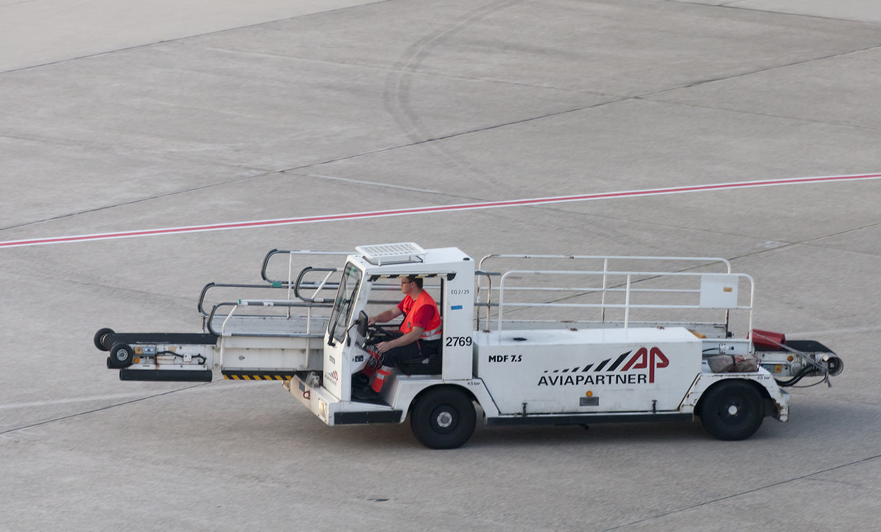 Airport ground technician driving vehicle for loading luggage into aircraft Airport Airport Runway Blue Collar Driving Driving Freight Transportation Full Length Land Vehicle Logistics Luggage Man Occupation One Man Only People Protective Workwear Runway Service Shipping  Side View Transportation Transportation Vehicle Worker Working Working
