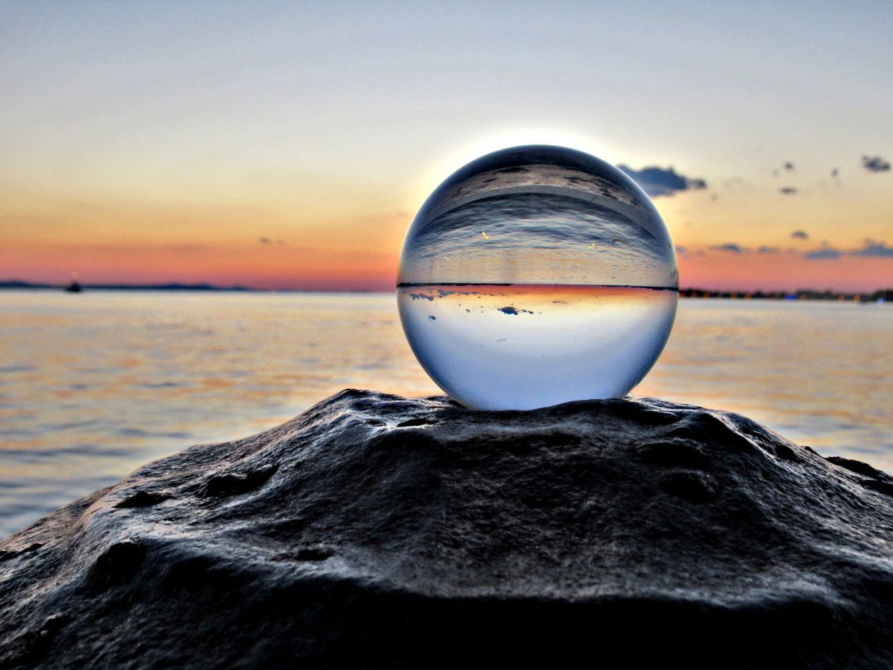 Close-Up Of Crystal Ball Against Sea During Sunset